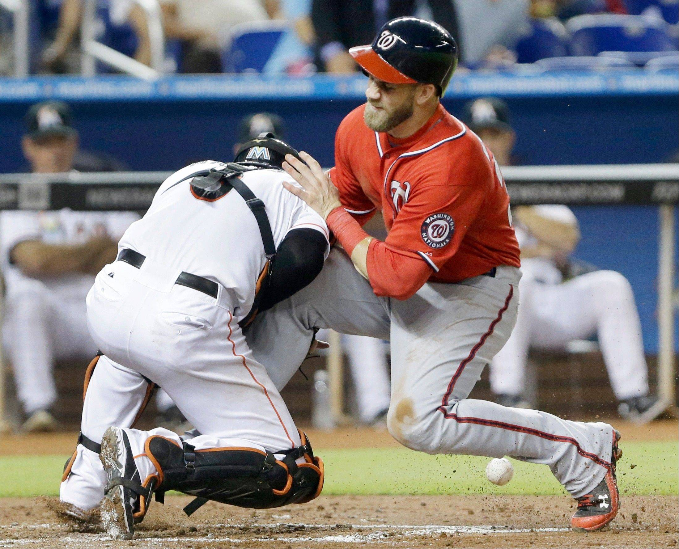 Washington Nationals outfielder Bryce Harper collides with Miami Marlins catcher Jeff Mathis at home plate Saturday during the fourth inning in Miami. Harper scored on a sacrifice fly by Jayson Werth.