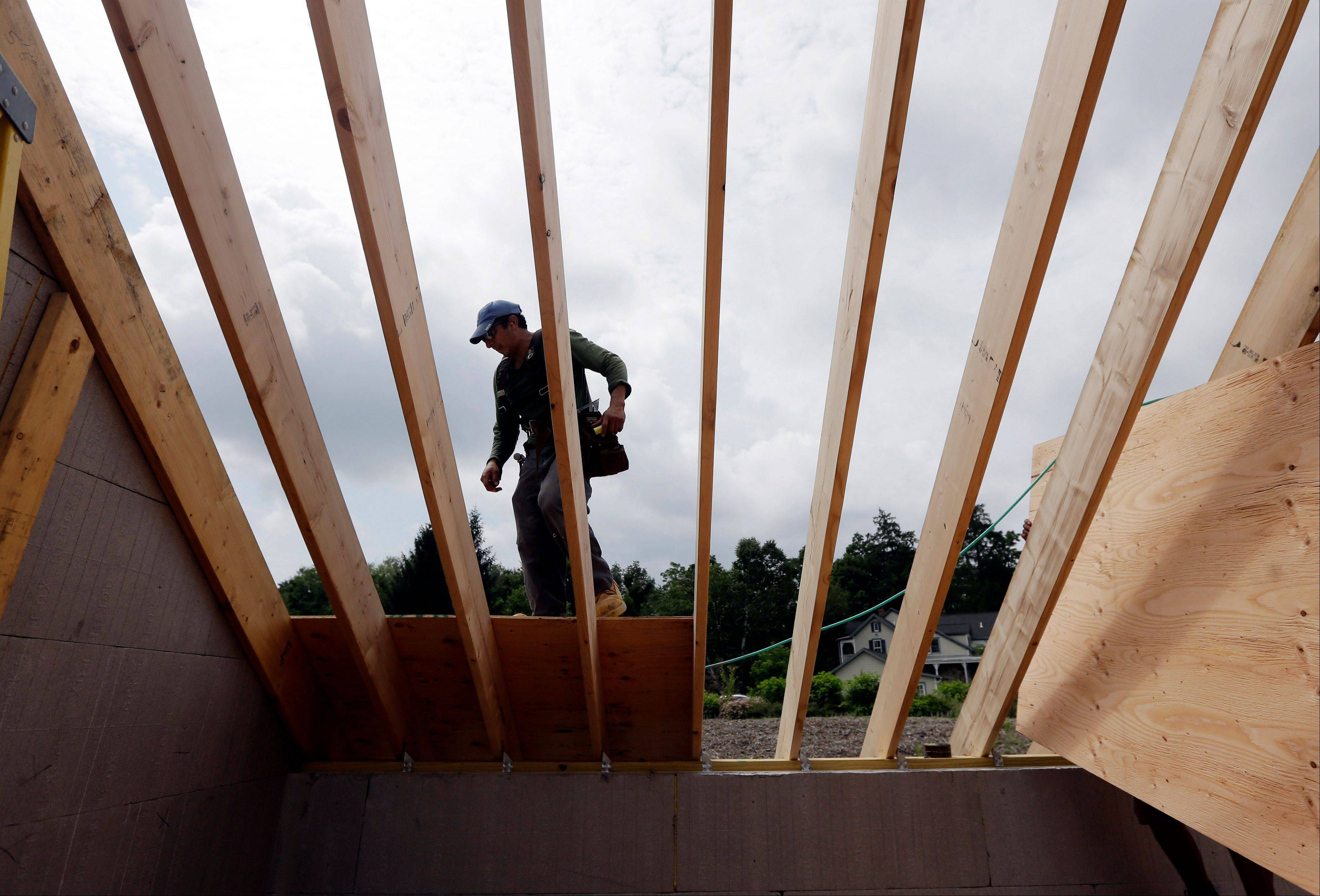 In this Tuesday, July 9, 2013, photo, a worker installs a roof on Tuesday, July 9, 2013, in New Paltz, N.Y. The National Association of Home Builders reports an increase in confidence among U.S. homebuilders for July on Tuesday, July 16, 2013.