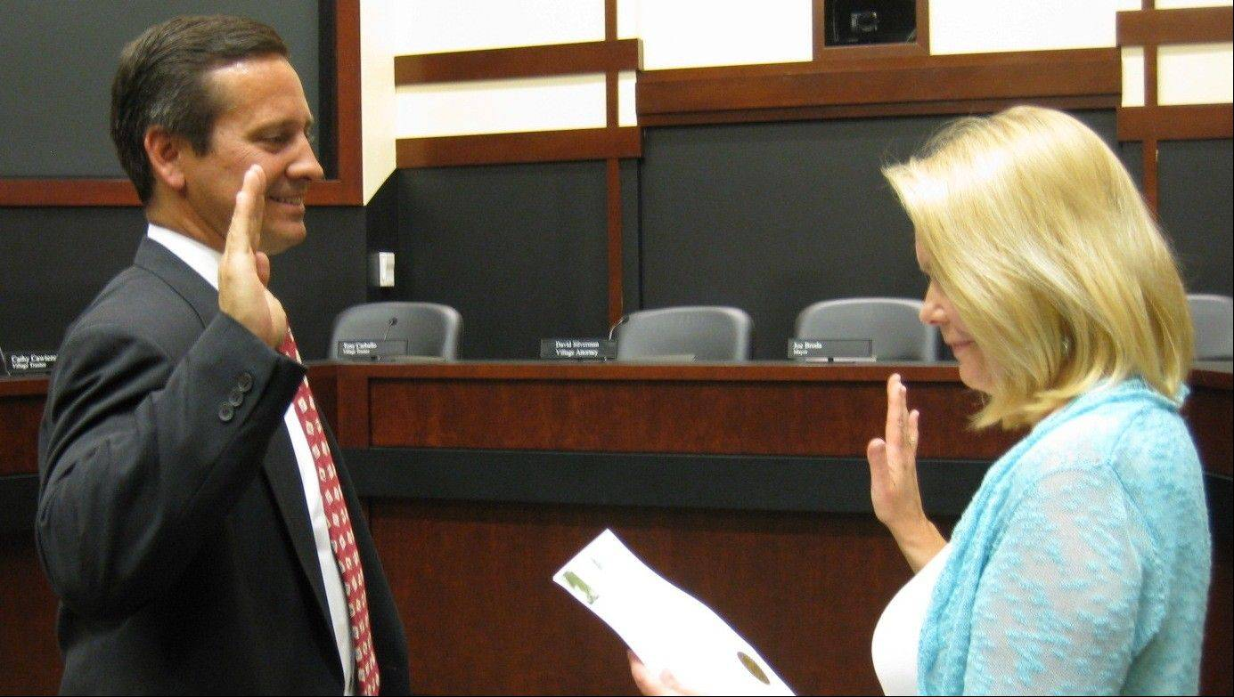 New Lisle village Trustee Bob Mandell takes the oath of office Monday from Deputy Clerk Kristine Curran.