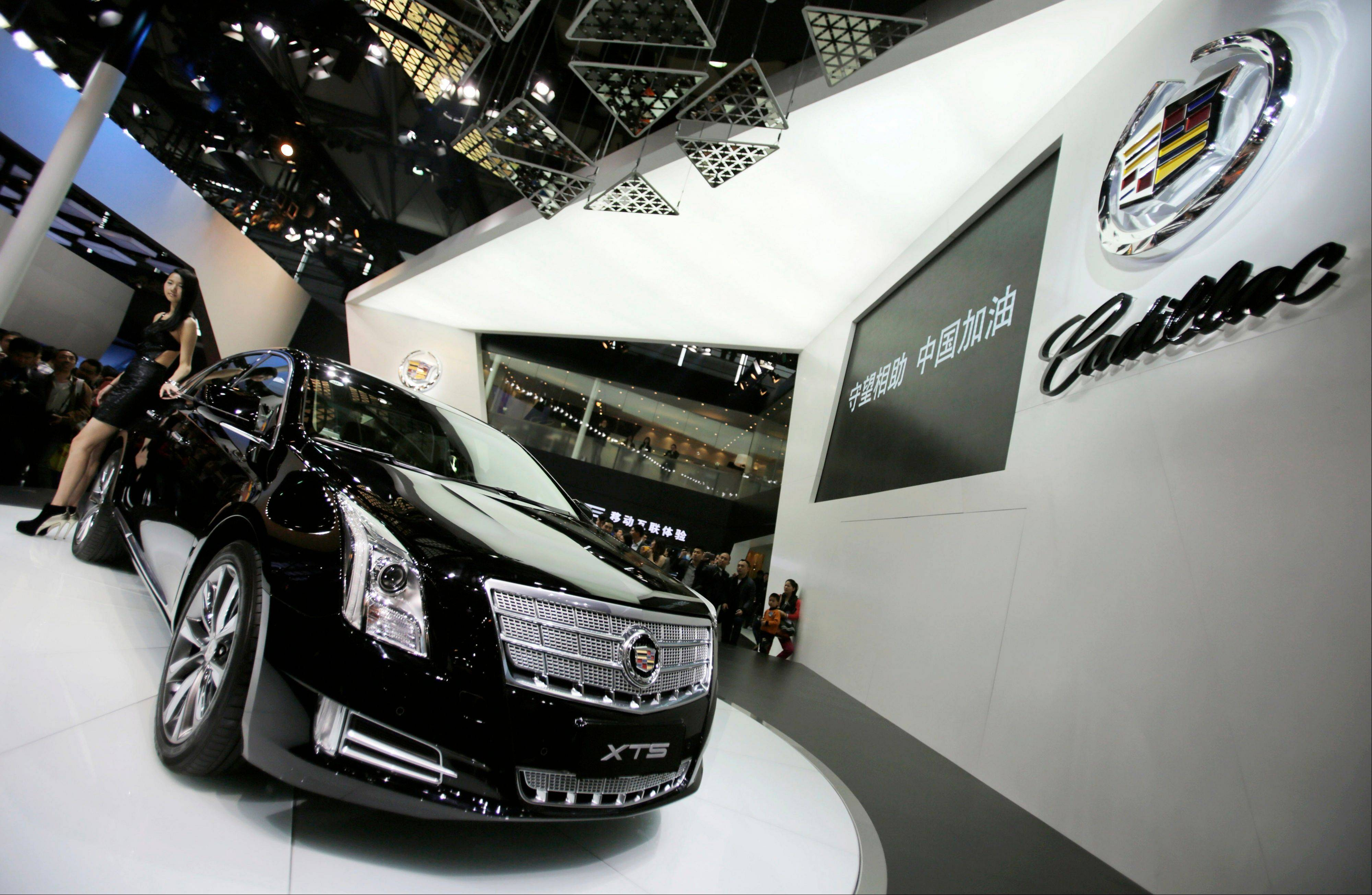 In this Sunday, April 21, 2013 photo, a model poses with a Cadillac XTS displayed at the Shanghai International Automobile Industry Exhibition in Shanghai, China. General Motors' global sales grew almost 4 percent in the first half of the year, enough to fend off Volkswagen to keep second place and perhaps bring the Detroit company closer to sales leader Toyota.