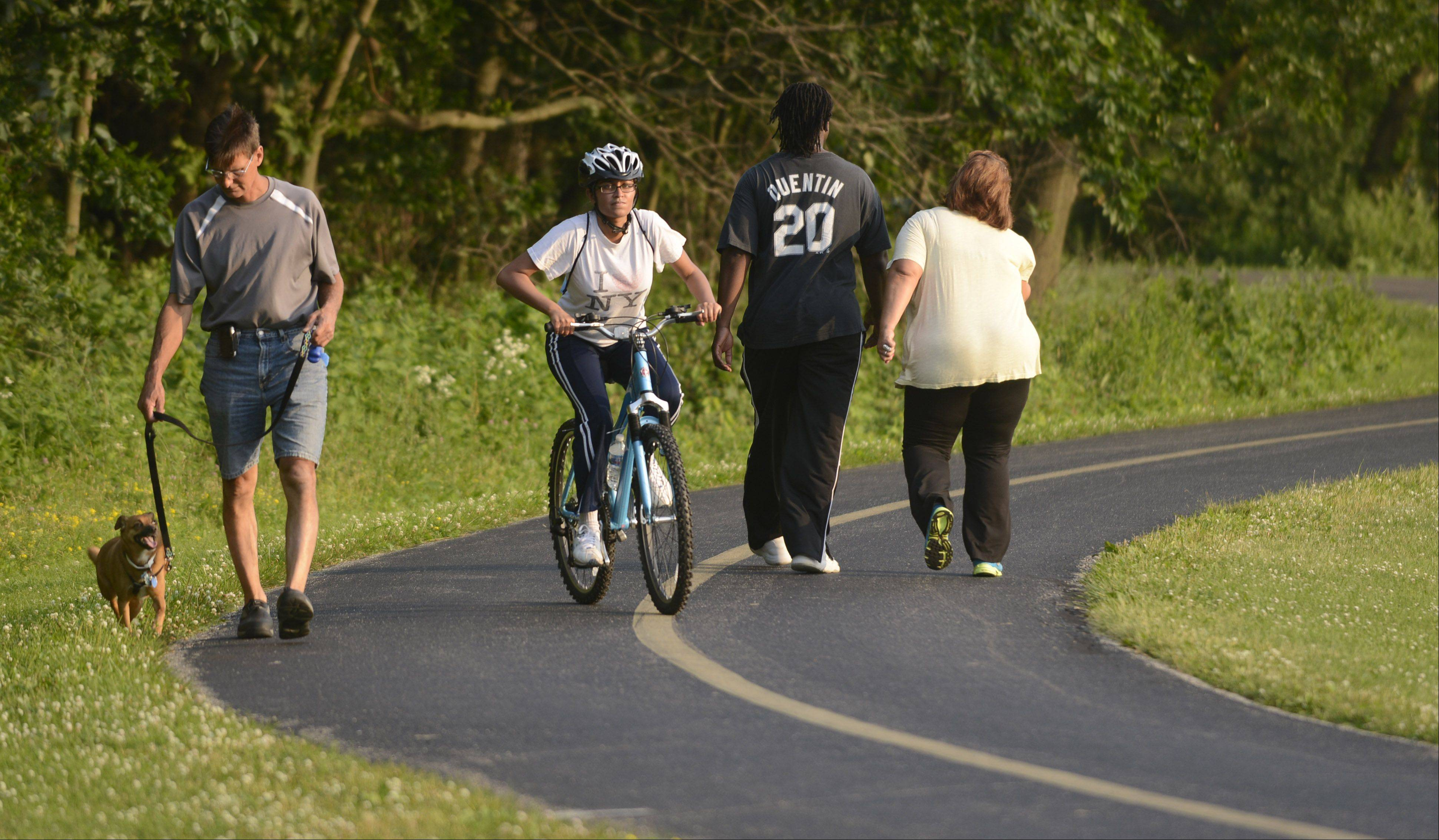A cyclist slows to ride past pedestrians on the Busse Woods bike path. Changes at the Lake Arlington trail could have implications for safety on other trails in the suburbs.