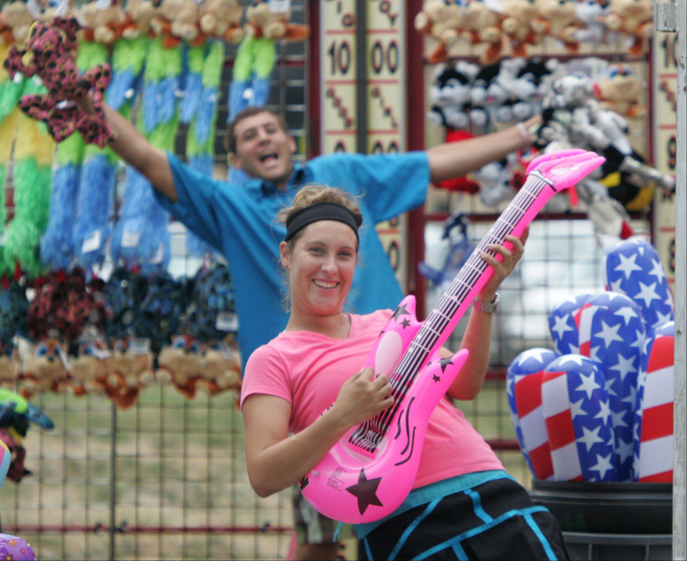 Lizanda Van Rooyen, of Alpine Amusement Co., plays air guitar while J.B. DuPlooy goofs off behind her as they try to attract customers to the Hammer Slammer game during a previous edition of the Antioch Taste of Summer Fest.