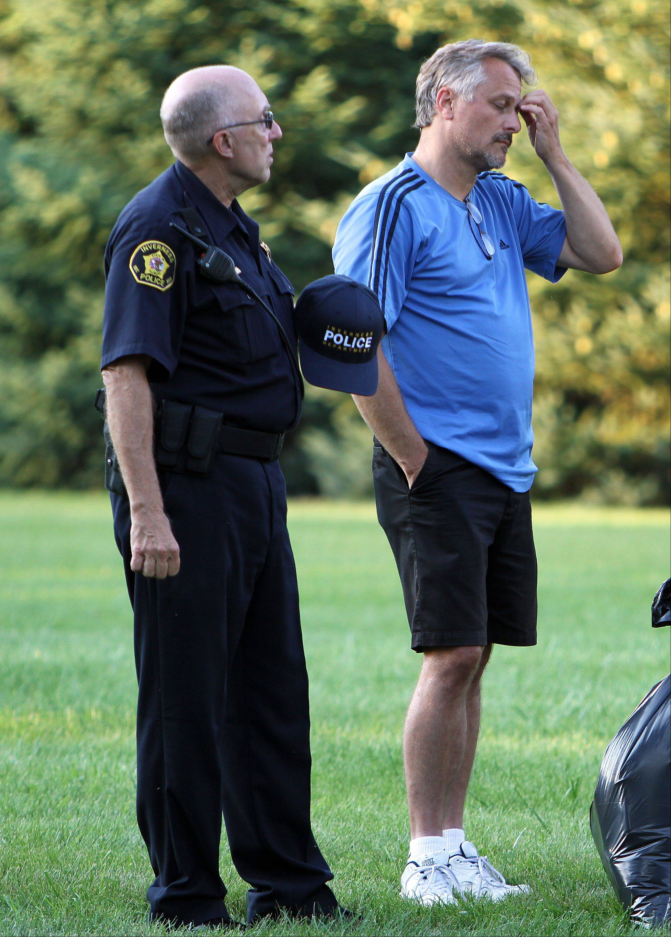 Inverness police officer Wes Gustafson, left, talks with homeowner Per Caesius as firefighters work to put out a fire that destroyed his home on Carnoustie Lane in Inverness Tuesday evening.