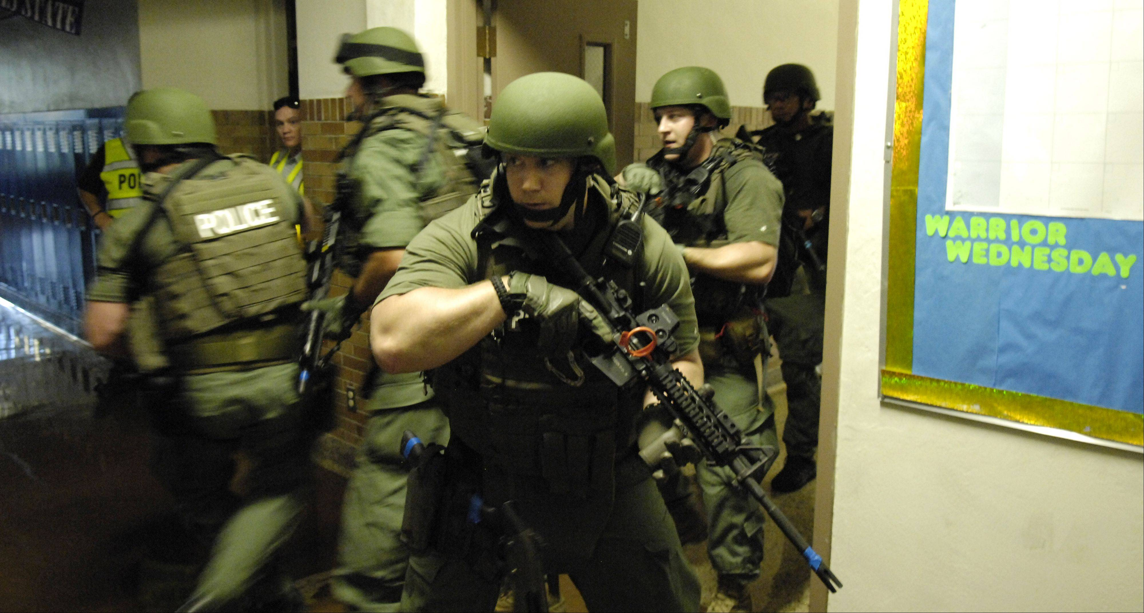Police and Elgin Area School District U-46 observers watch from a corner as the Elgin Police SWAT team does a room to room search during a simulated school security breach exercise Tuesday at Abbott Middle School. The scenario included a shooting situation, mock injuries, lockdown, police rapid deployment, building clearing and post-incident debriefing.