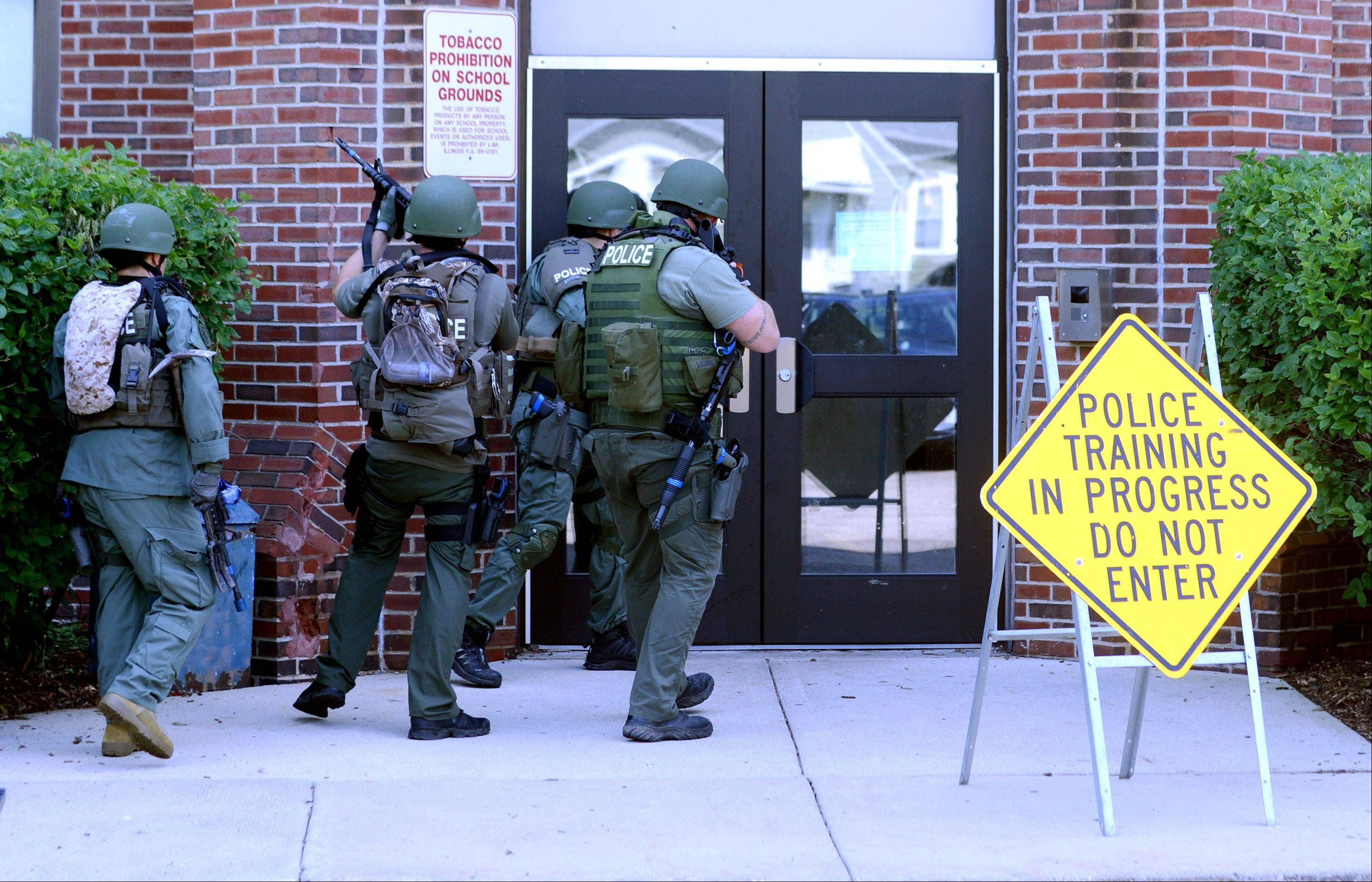 The Elgin Police SWAT unit prepares to enter Abbott Middle School during a simulated school security breach exercise Tuesday completed in partnership with the Elgin Fire Department.