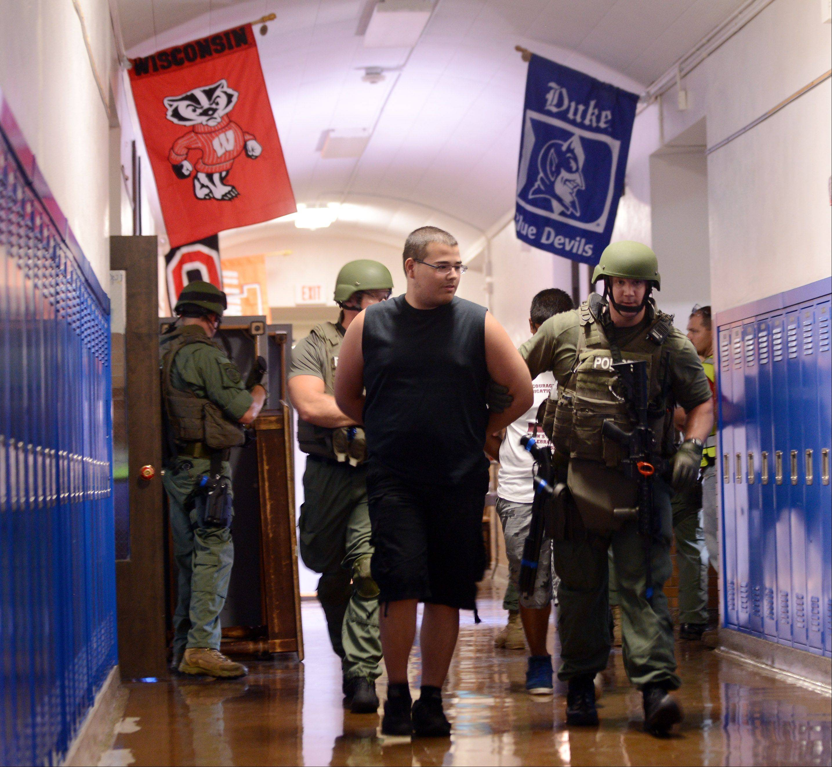 "A ""suspect"" is taken into custody Tuesday during a simulated school shooting at Abbott Middle School in Elgin. Elgin Area School District along with the police and fire departments took part in an exercise that included a shooting situation, mock injuries, lockdown, police rapid deployment, building clearing and post-incident debriefing."