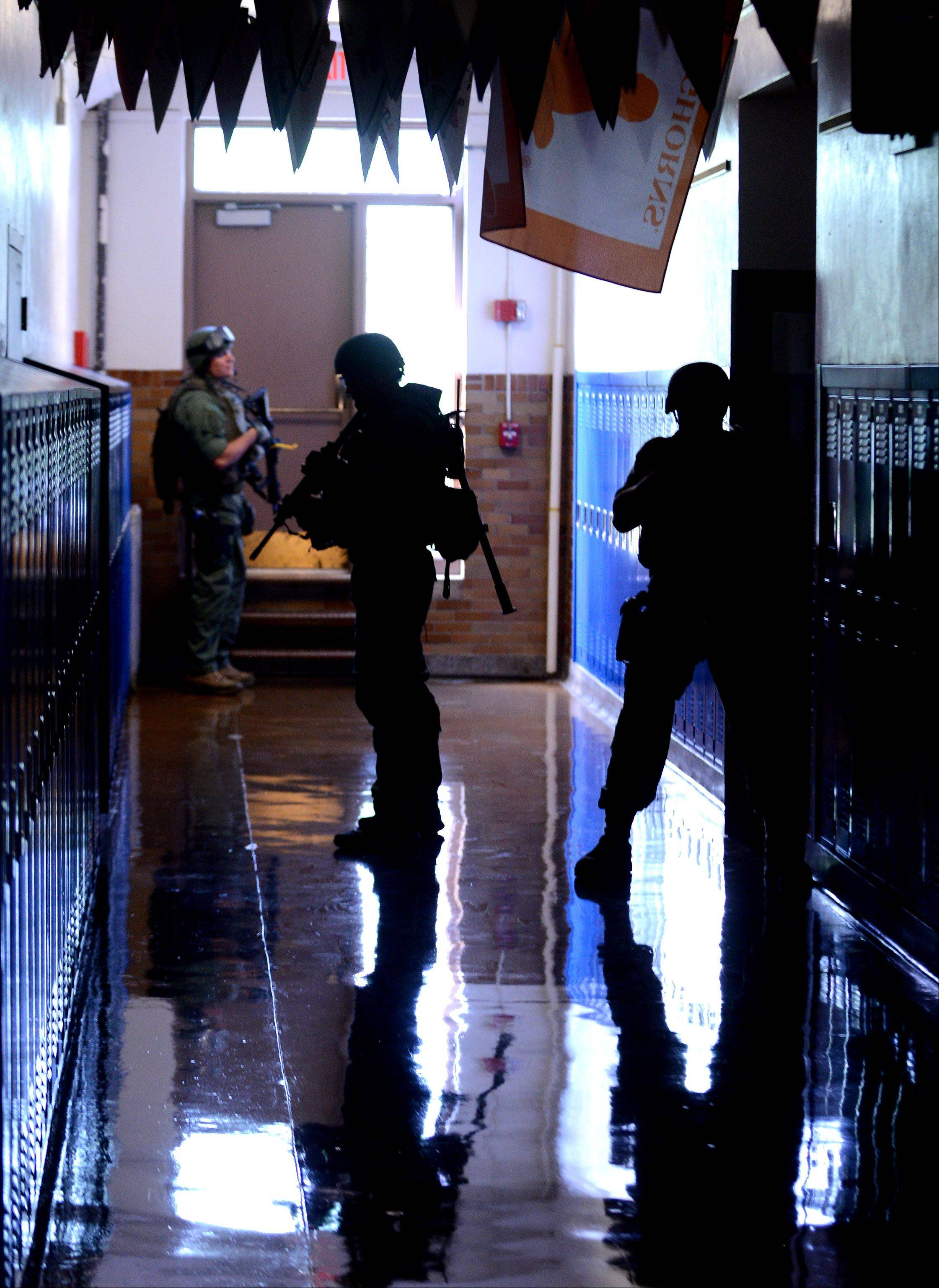 Elgin Police SWAT members do a room by room sweep during a security exercise involving a simulated shooting Tuesday at Abbott Middle School.