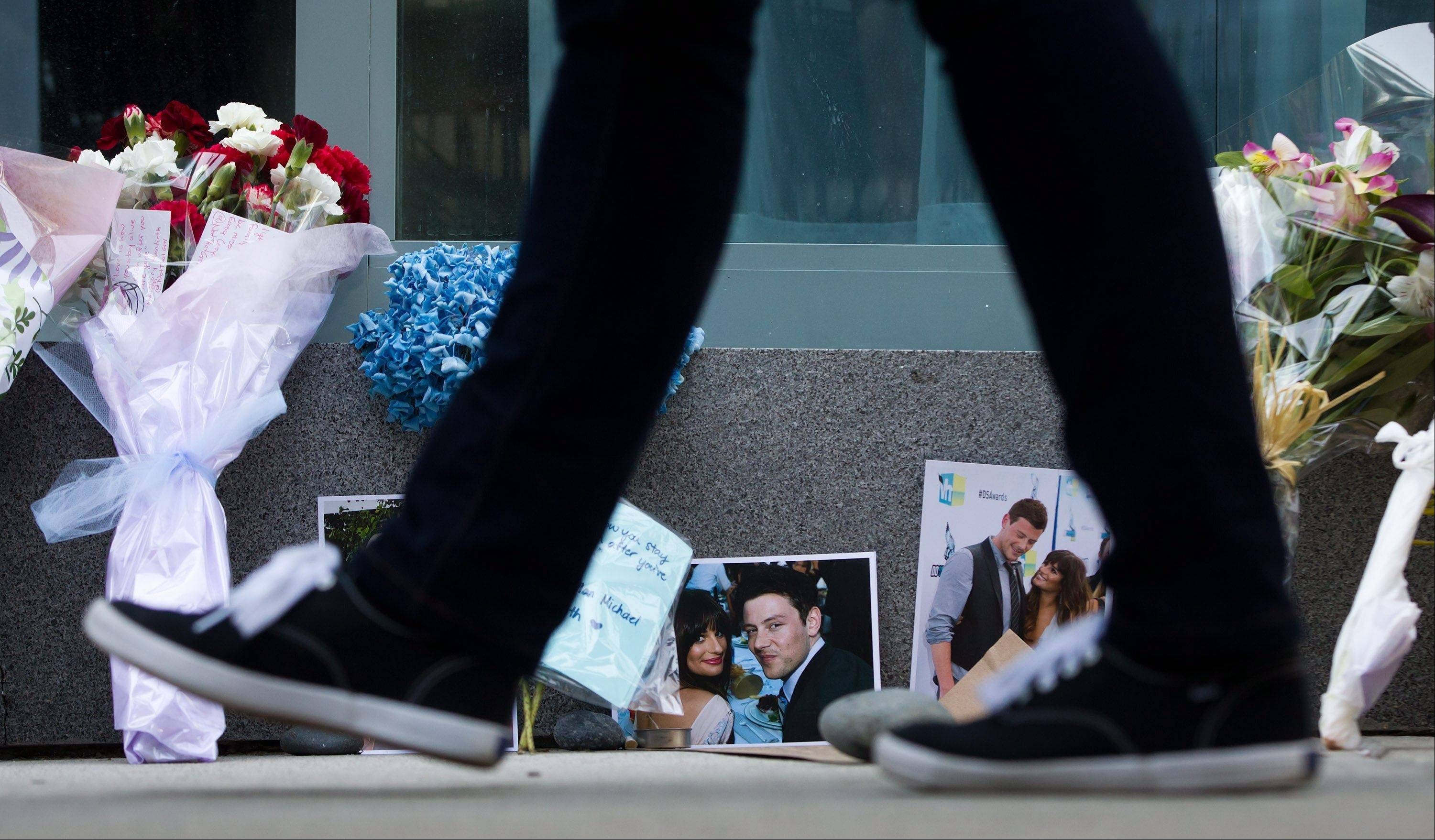 A pedestrian walks past photographs and flowers placed at a memorial for Canadian actor Cory Monteith outside the Fairmont Pacific Rim Hotel in Vancouver, British Columbia. Monteith, 31, was found dead in his room at the hotel on Saturday. The Vancouver coroner says he died from an overdose of heroin and alcohol.