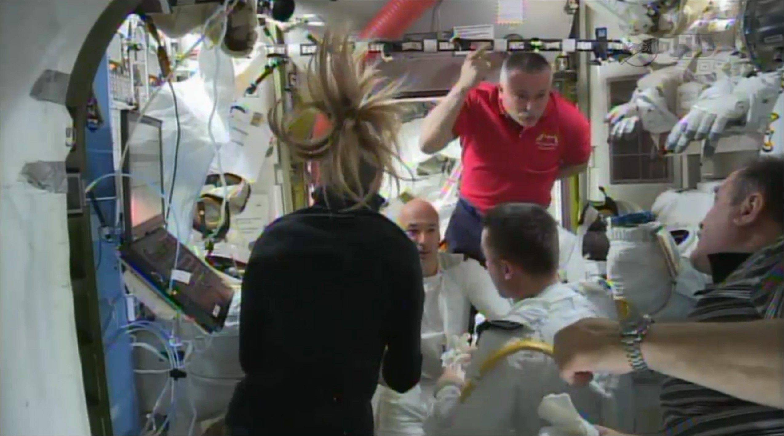 In this image from video made available by NASA, astronauts discuss the aborted spacewalk aboard the International Space Station on Tuesday. A dangerous water leak in the helmet of Luca Parmitano, bottom center facing camera in white suit, drenched his eyes, nose and mouth, preventing him from hearing or speaking as what should have been a routine spacewalk came to an abrupt end.