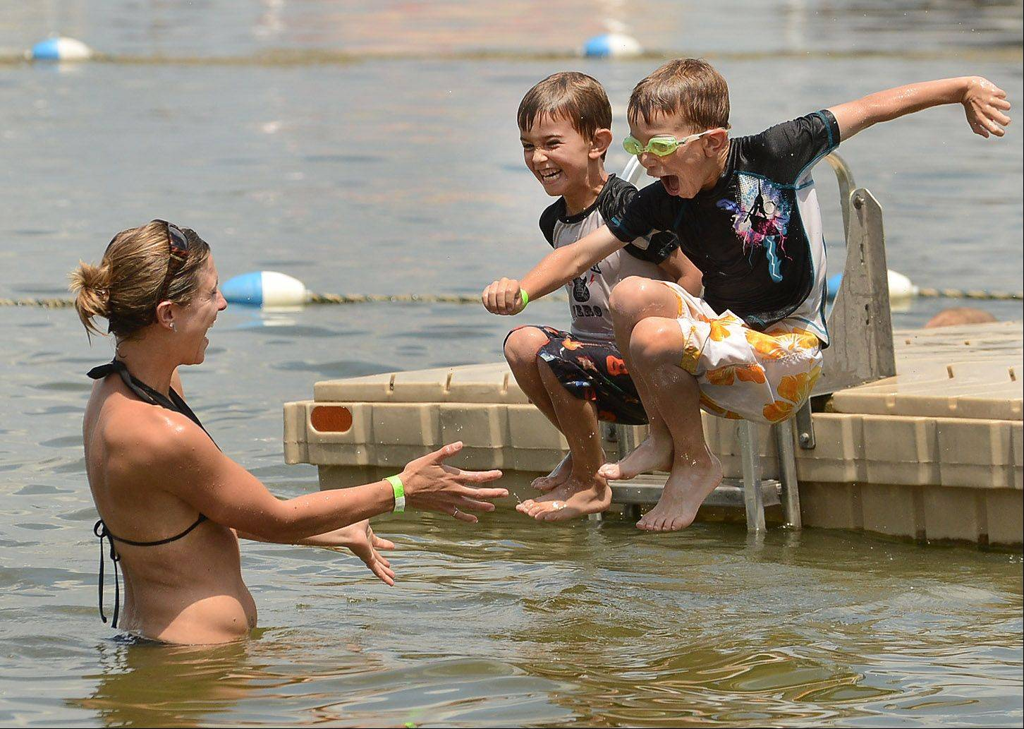 Payton Harlow, left, and his brother, Logan, of Island Lake jump toward their mom, Katie Harlow, at Bangs Lake in Wauconda.