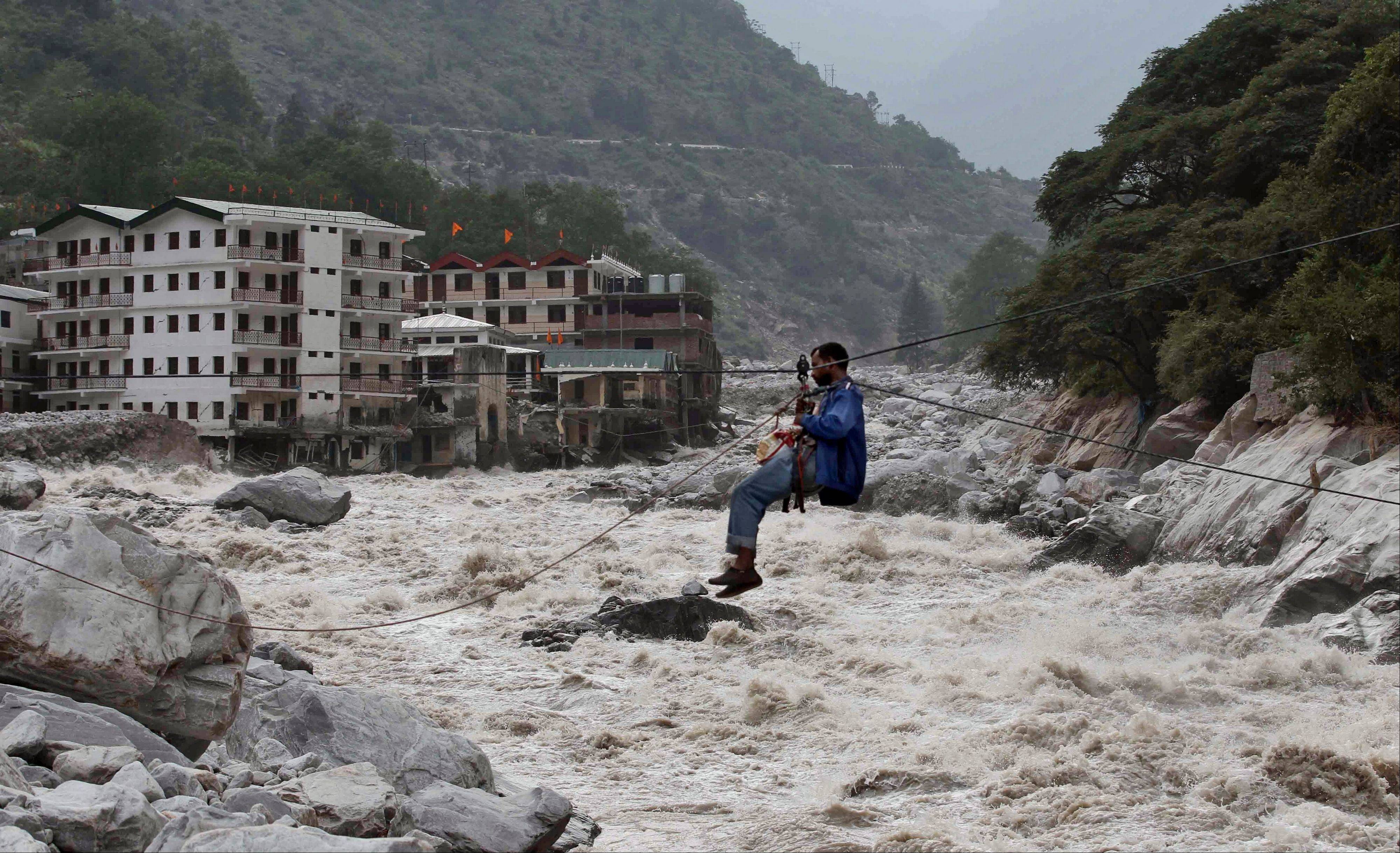 In this June 23 photo, an Indian man crosses over a swollen river with the help of a rope in Govindghat, in the northern India state of Uttarakhand, India. A top Indian official said more than 5,700 people missing since last month's devastating floods that ravaged northern India are now presumed dead.