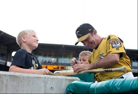 Recognizing how much his minor league baseball team means to kids and others in the community, Southern Illinois Miners Manager Mike Pinto autographs a bat for a happy boy.