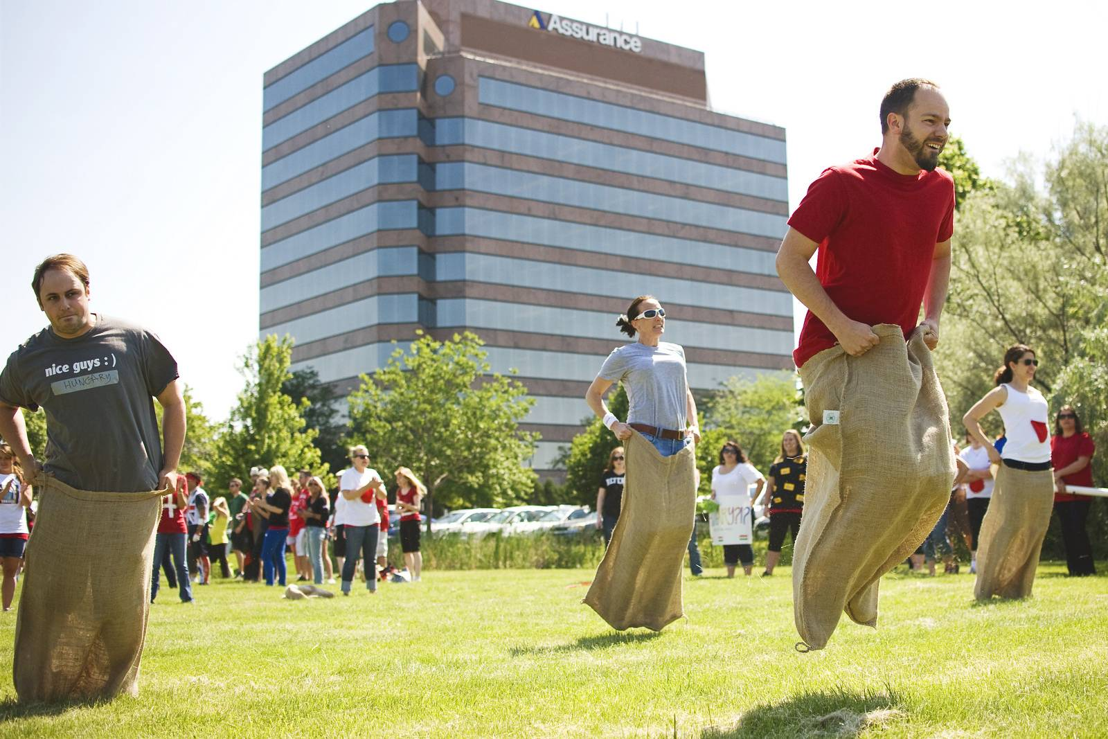 Jim Andrews (with beard) of Elgin, graphic design specialist at Assurance, has a commanding lead in the Potato Sack Race during the annual Assurance Olympics, held to promote corporate wellness on Wednesday, June 19, at company headquarters in Schaumburg. Not far behind are (from left): Ben Kachelmuss of Volo, office and facilities coordinator; Natalie Loechl of Algonquin, senior client service representative; and Talicia Bashford of Palatine, client services director.