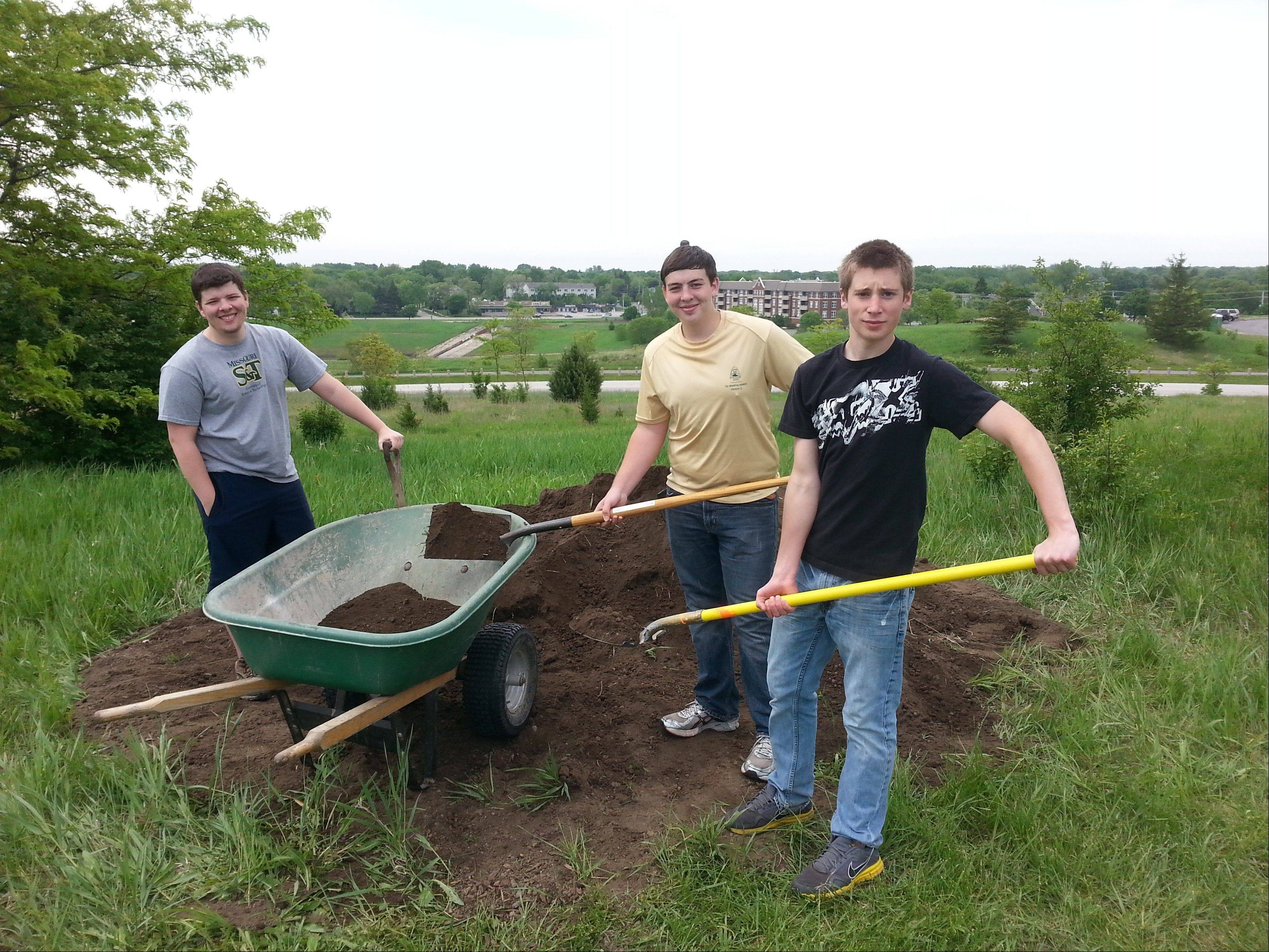 Troop 335 Eagle Scout candidate Casey Wagner, pictured, far right, along with fellow scouts, work at the Margreth Riemer Reservoir in Palatine helping ready the disc golf course for expansion.