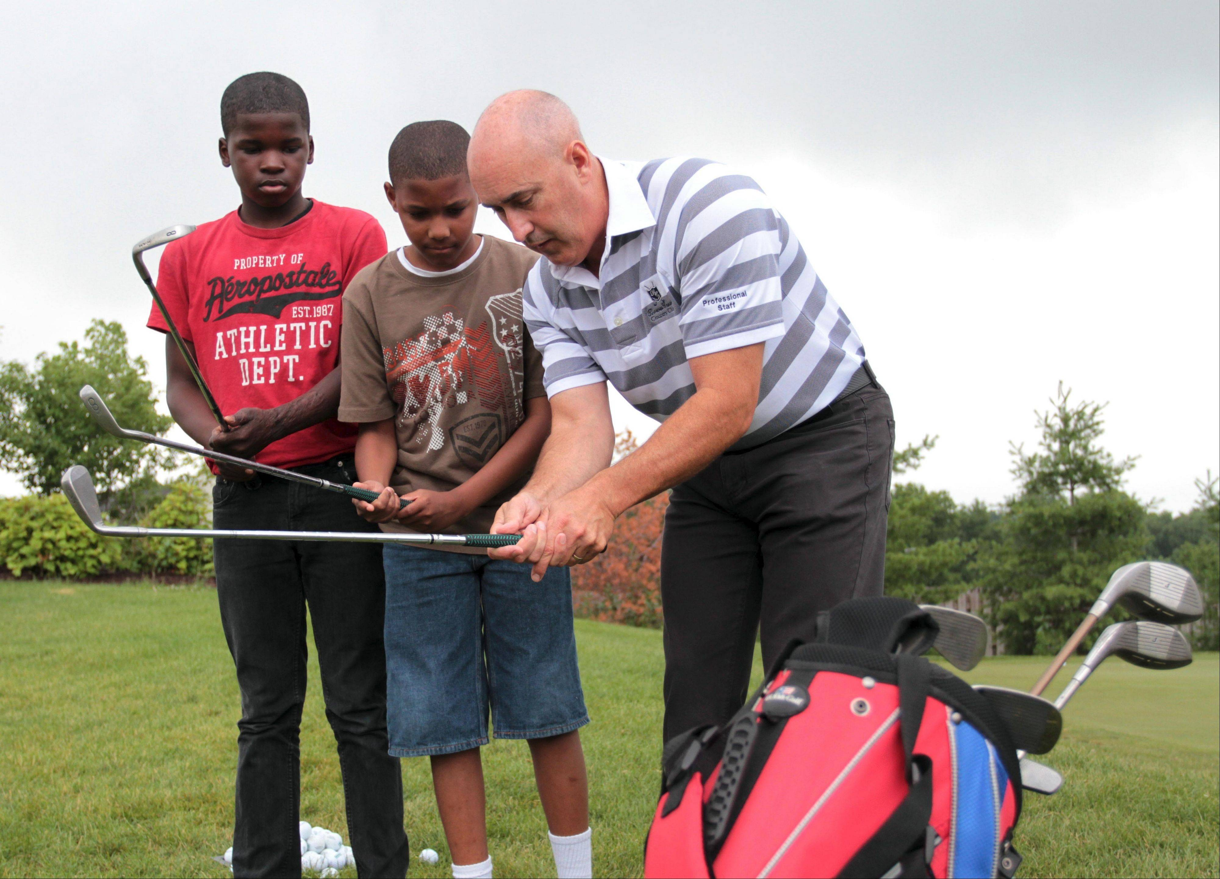 Mike Lehman, director of operations and head golf professional at Bowes Creek Country Club in Elgin, instructs Trey Morris and Damarion Benton, both of Elgin, when they received their clubs from The Sports Shed for the PGA Medalist Golf Camp.
