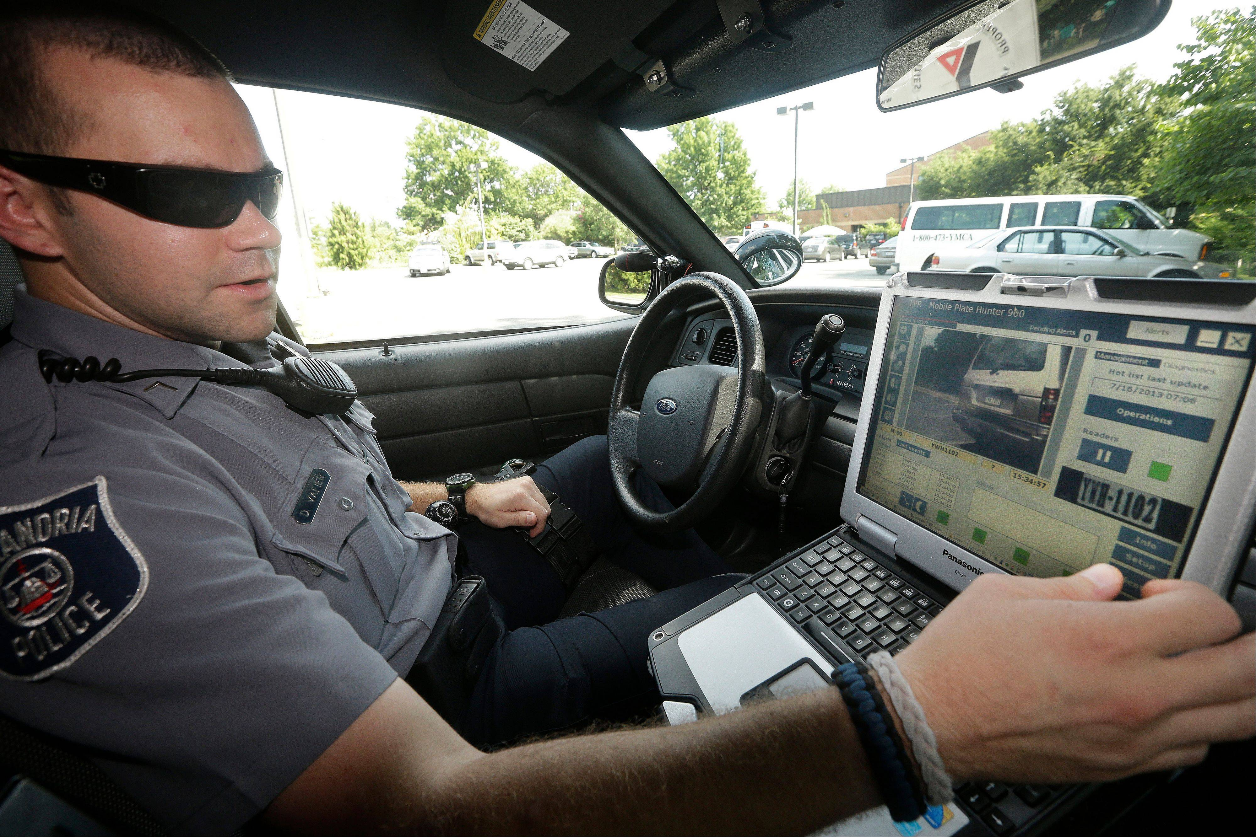 Office Dennis Vafier of the Alexandria Police Dept., uses a laptop in his squad car to scan vehicle license plates during his patrols, Tuesday, July 16, 2013 in Alexandria, Va. Local police departments across the country have amassed millions of digital records on the location and movements of vehicles with a license plate using automated scanners.