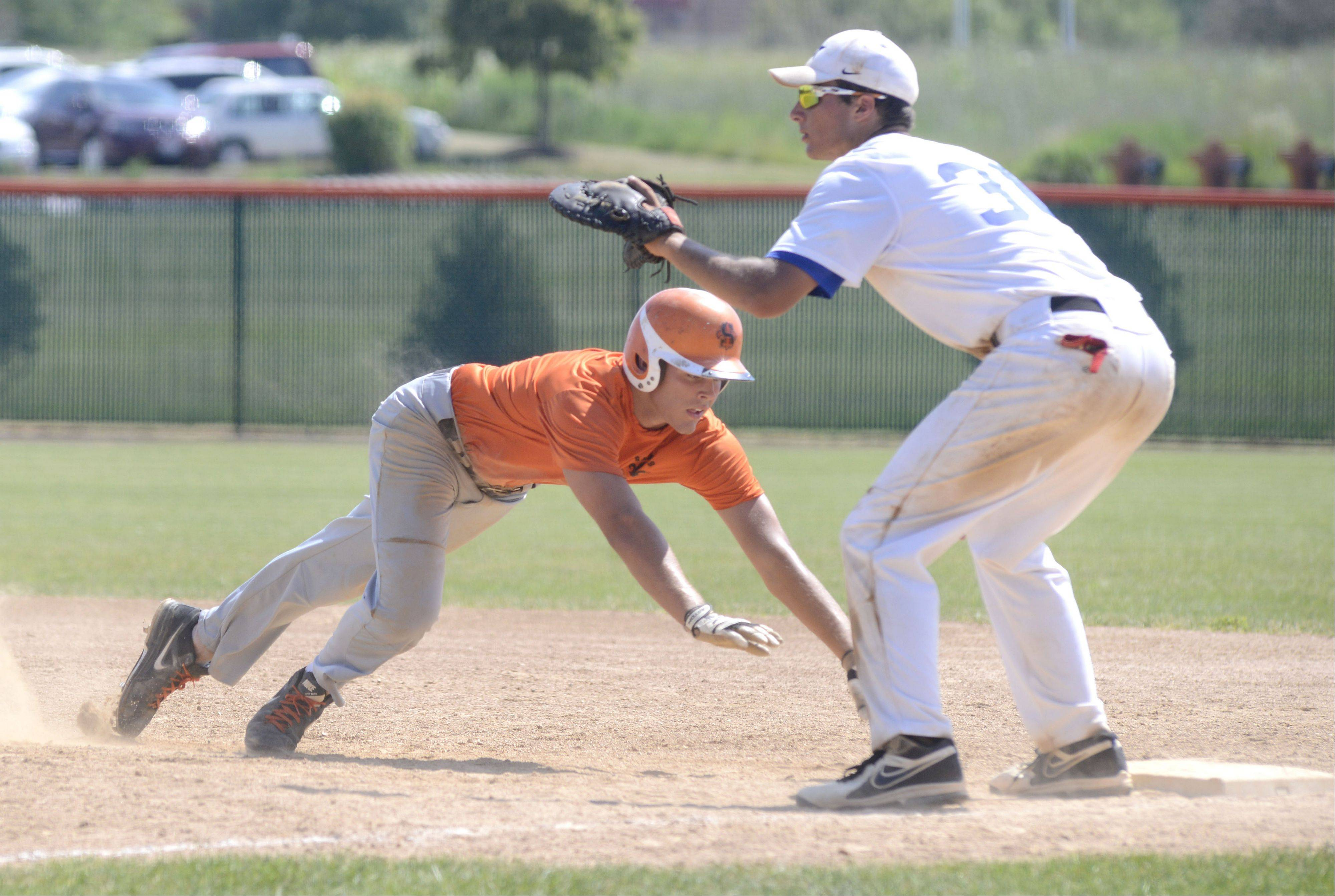 St. Charles East�s Erik Anderson dives back safely to first base before St. Charles North�s Joe Kuczek can tag him out in the fourth inning of the St. Charles East summer tournament semifinals on Wednesday, July 17.