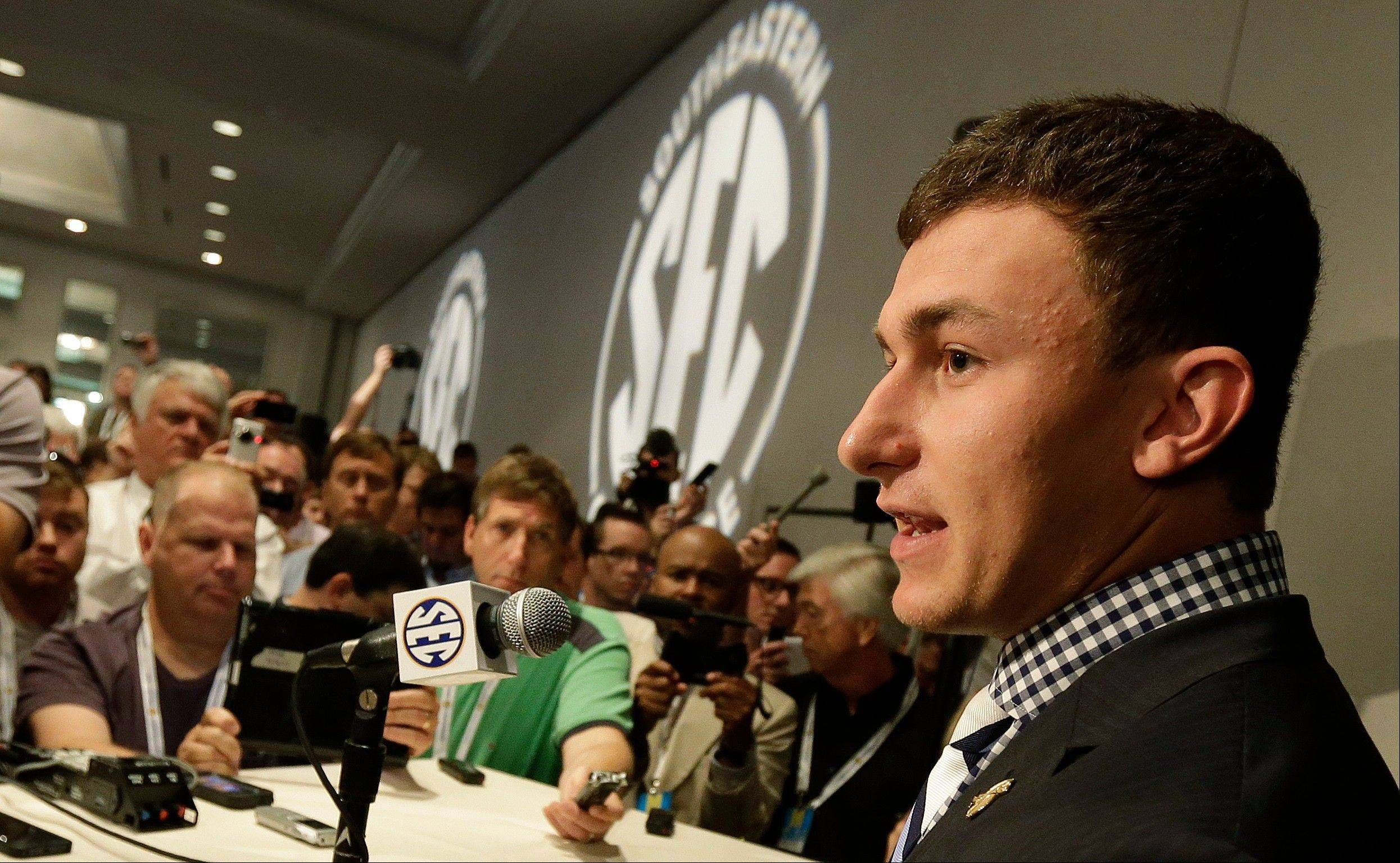 Texas A&M quarterback Johnny Manziel talks with reporters Wednesday during the Southeastern Conference football Media Days in Hoover, Ala.