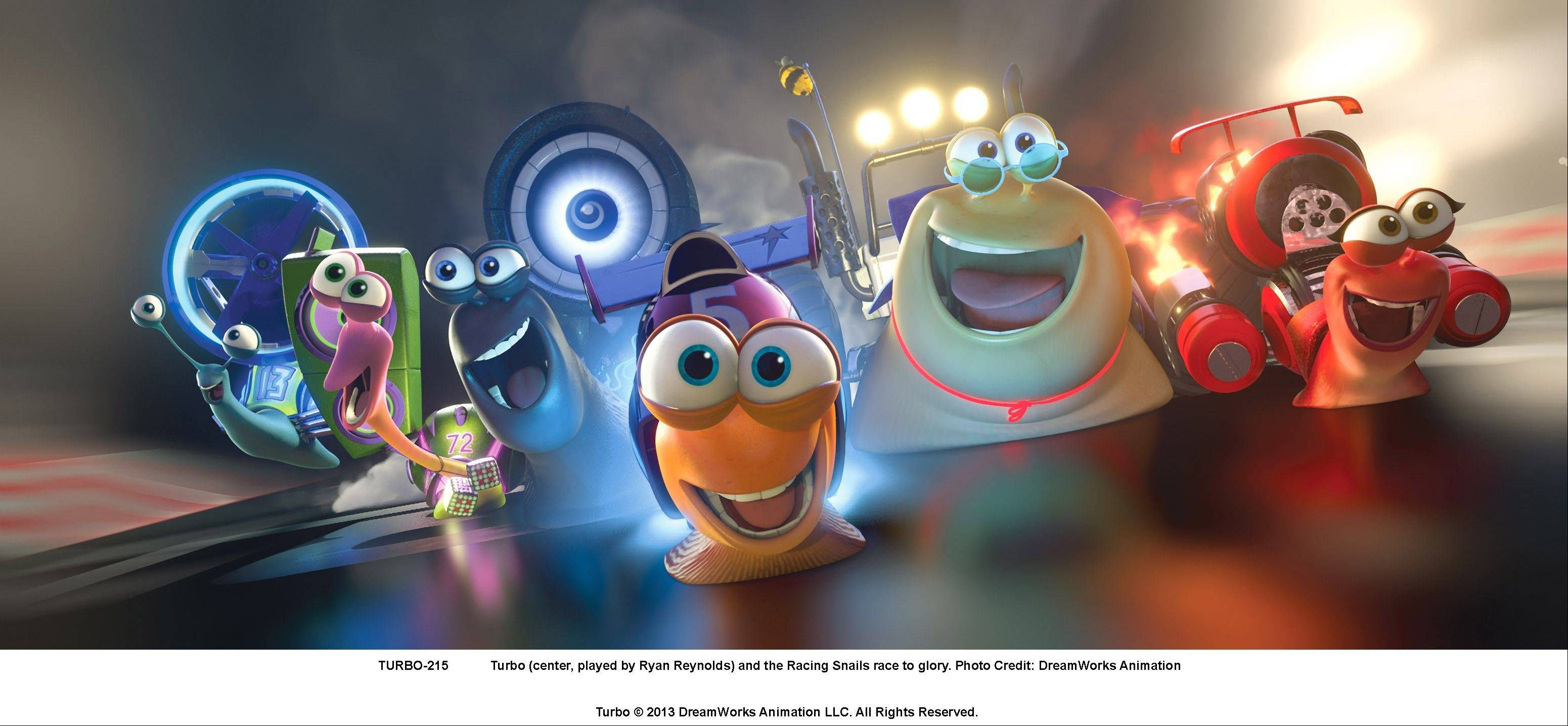 "Turbo (the orange snail voiced by Ryan Reynold), center, leads his race team to victory in the animated comedy ""Turbo."""