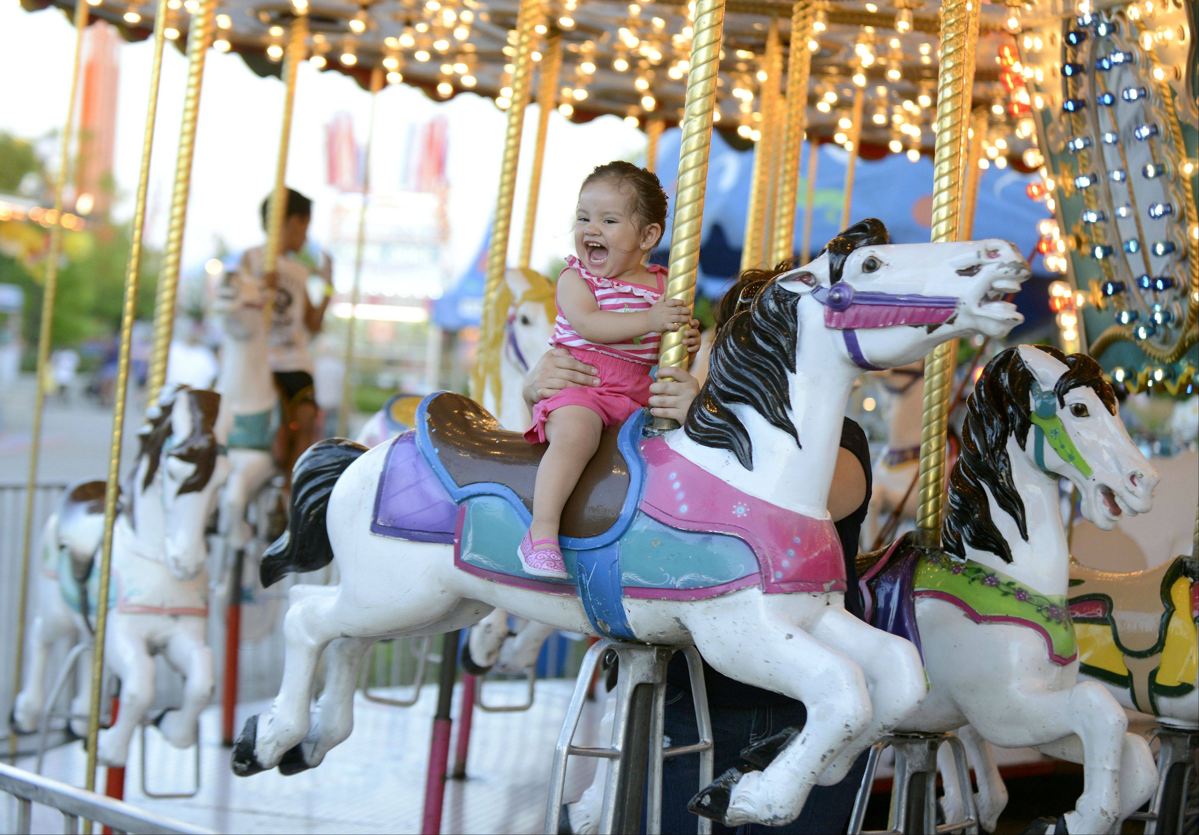 Leah Cruz, 18 months, of Elgin squeals with delight after seeing her father while she and her mother, Janessa, (unseen, holding her on) take a ride on the Merry-go-round at the Kane County Fair in St. Charles on Wednesday, July 17.