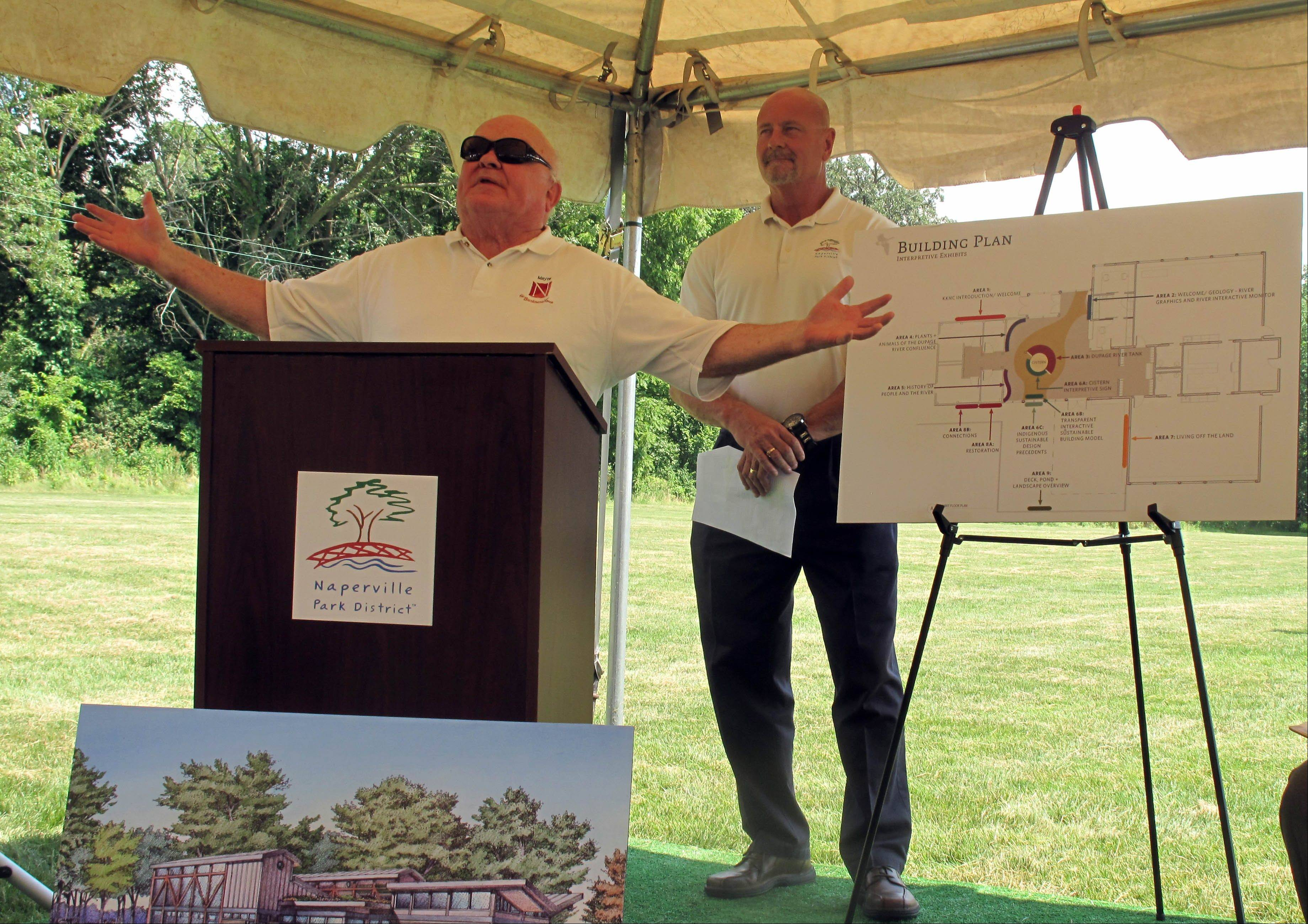 "Naperville Mayor George Pradel takes the stage from Naperville Park District Executive Director Ray McGury Wednesday as the park district breaks ground on its first staffed nature center, a facility with the theme ""Celebrating water"" at Knoch Knolls park."