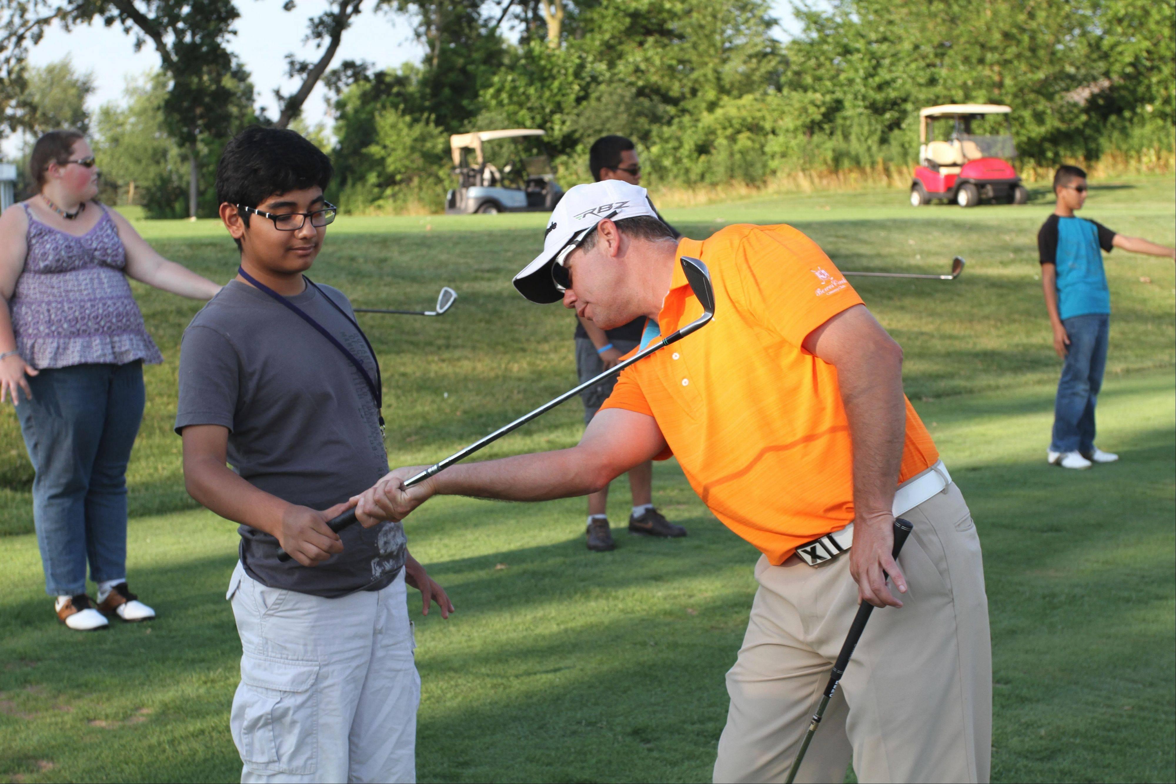 Bowes Creek golf pro Kurt McCullon instructs Alexis Campuzano on how to properly grip a golf club at the PGA Medalist Golf Camp.