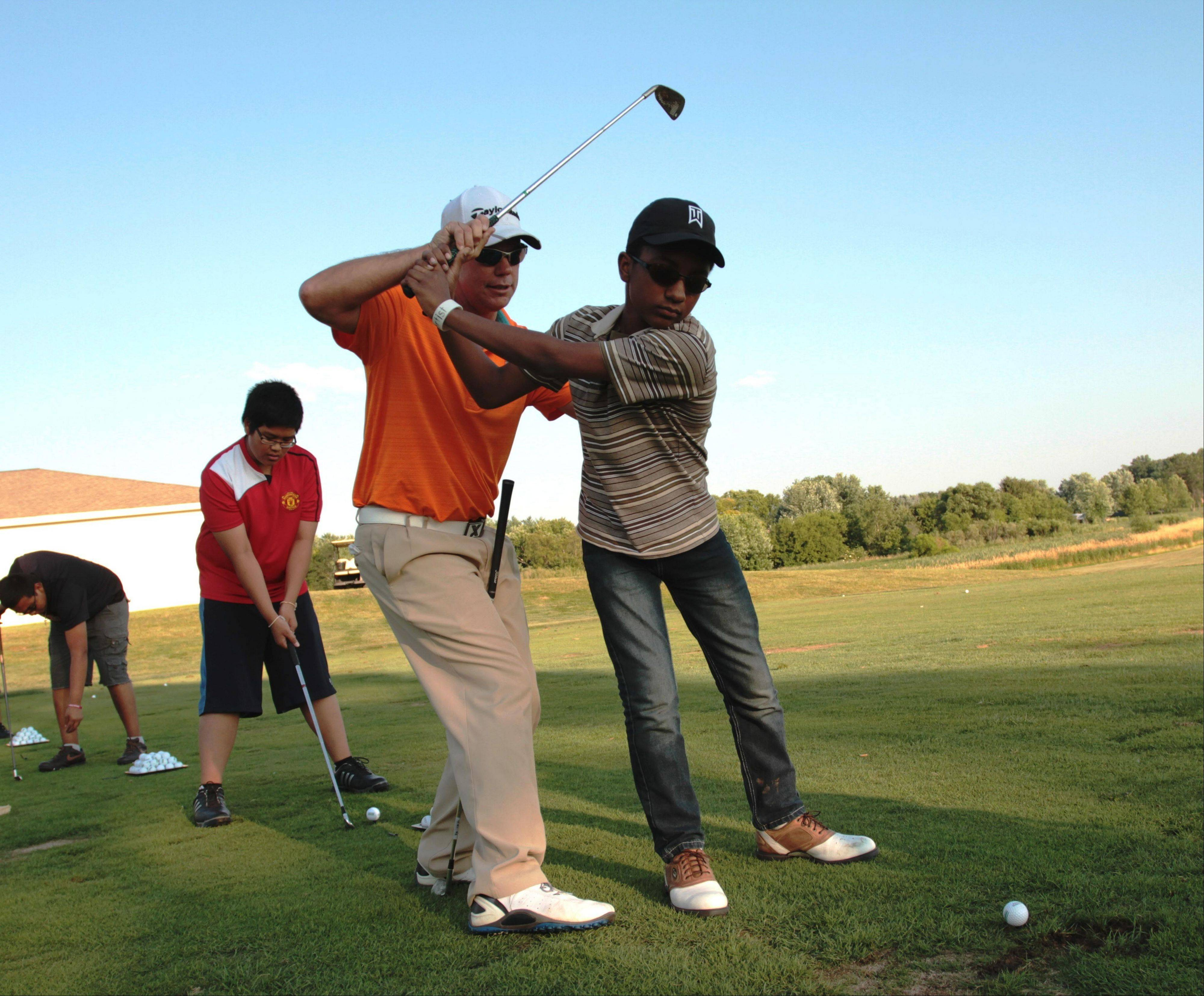 Bowes Creek pro Kurt McCullon instructs Romero Golden-Garcia on his golf swing last week at the PGA Medalist Golf Camp.