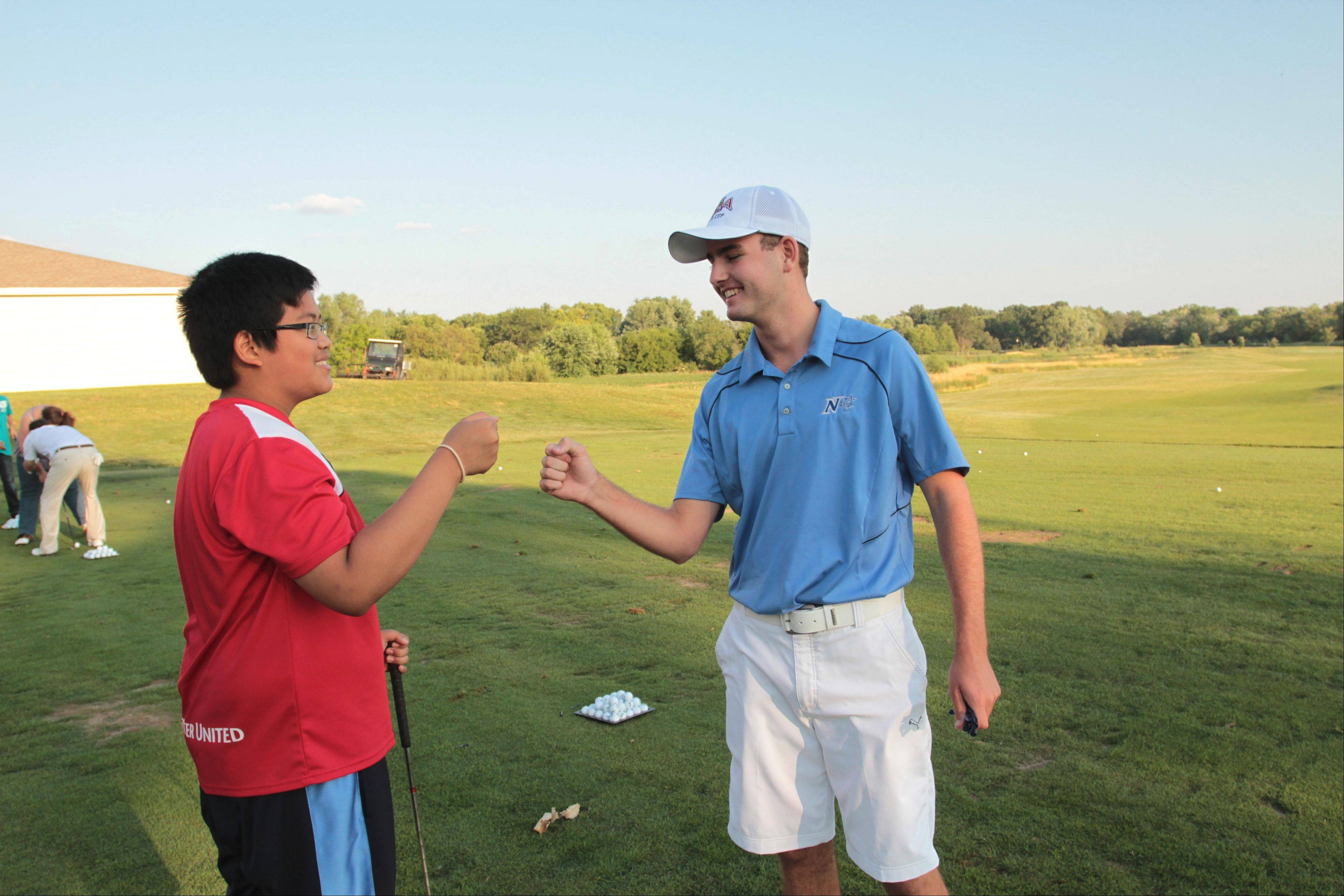 Jeff Phoulavona, left, appreciates the lesson from St. Charles North High School graduate Ryan Del Degan at the PGA Medalist Golf Camp.