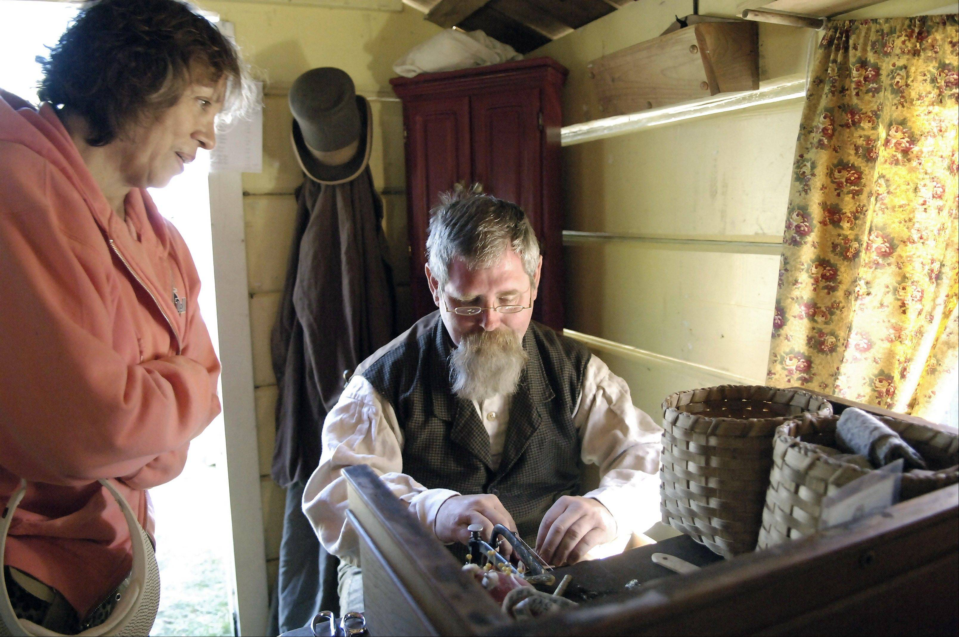 Rose Milo of Algonquin watches re-enactor Ken Gough of Elgin use an 1854 Wheeler and Wilson lockstitch sewing machine in an 1860s era cabin during a Civil War encampment at the 2008 Heritage Fest in West Dundee. This year, East Dundee and West Dundee will co-host the fest.
