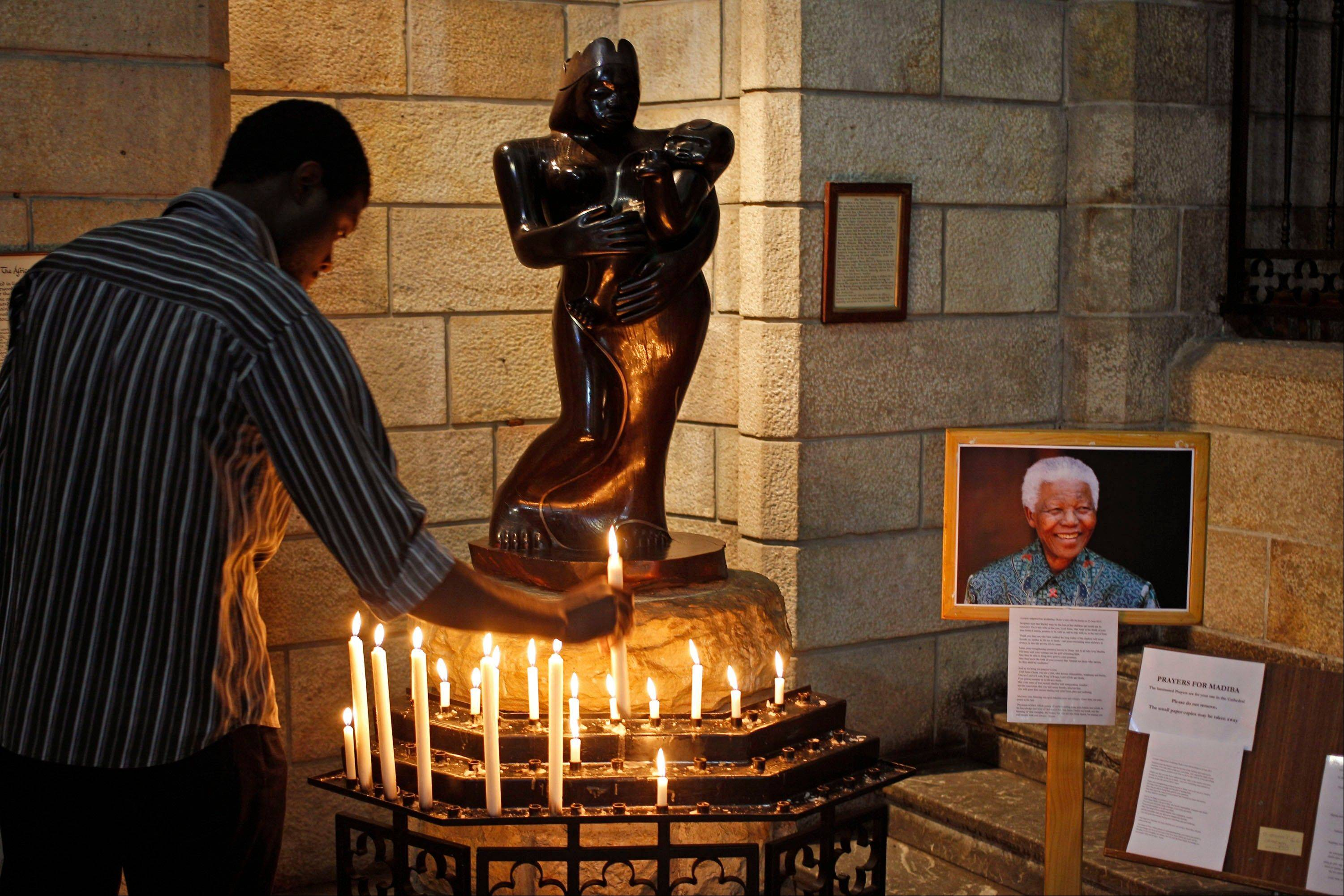 A man places a candle after he prayed for former South African President Nelson Mandela inside the St. George's Cathedral in Cape Town, South Africa, Wednesday, July 17, 2013.