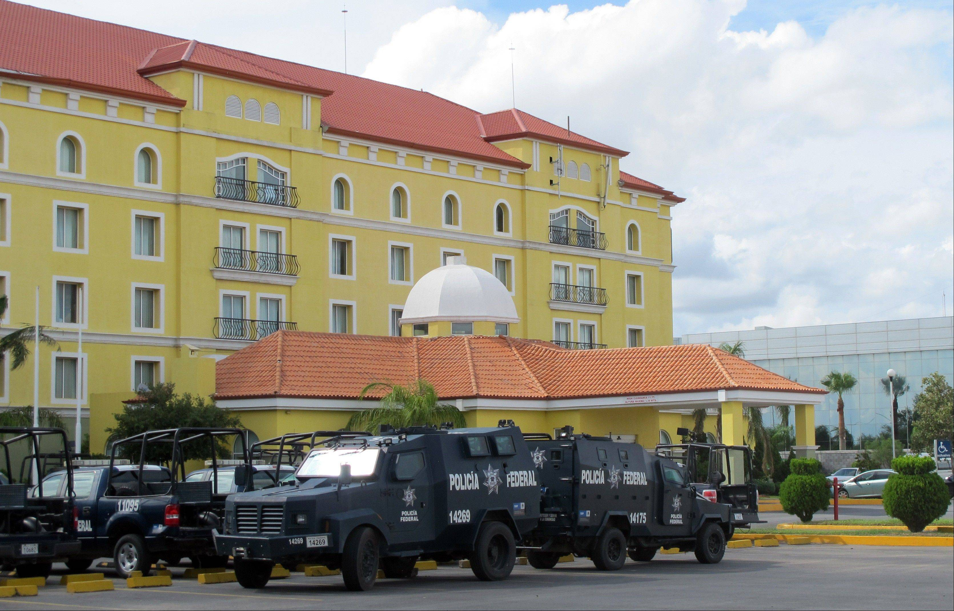 Police vehicles sit parked outside a hotel in Nuevo Laredo, Mexico, Tuesday, July 16, 2013. Local hotels are housing many of the federal police, state police and members of the armed forces who patrol the northern border city, which is home to the Zetas organized crime group.
