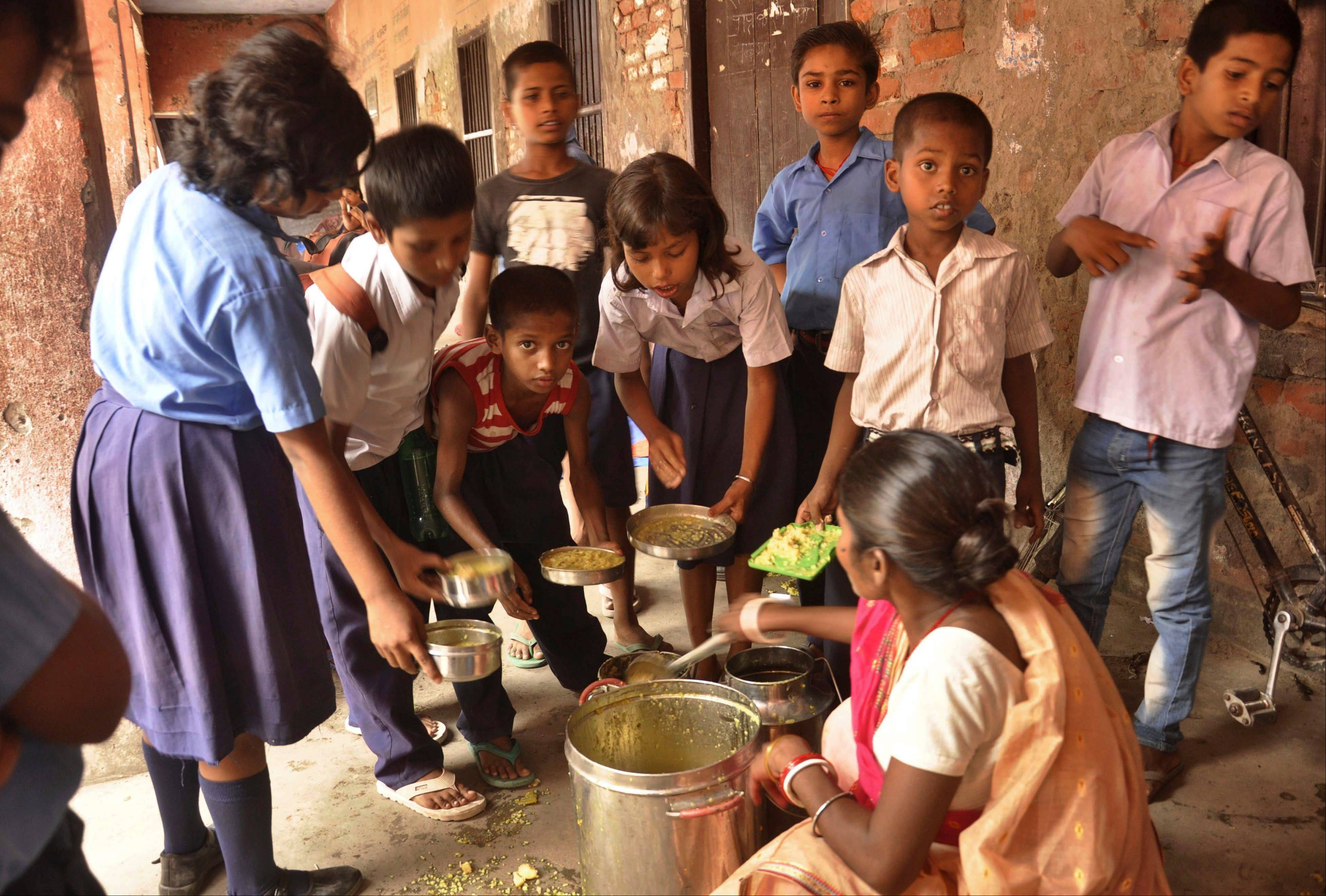 An Indian cook distributes free school lunches to children at a government run school in Patna, India, Wednesday. On Tuesday, at least 22 children died and more than two dozen others were sick after eating a free school lunch that was tainted with insecticide.