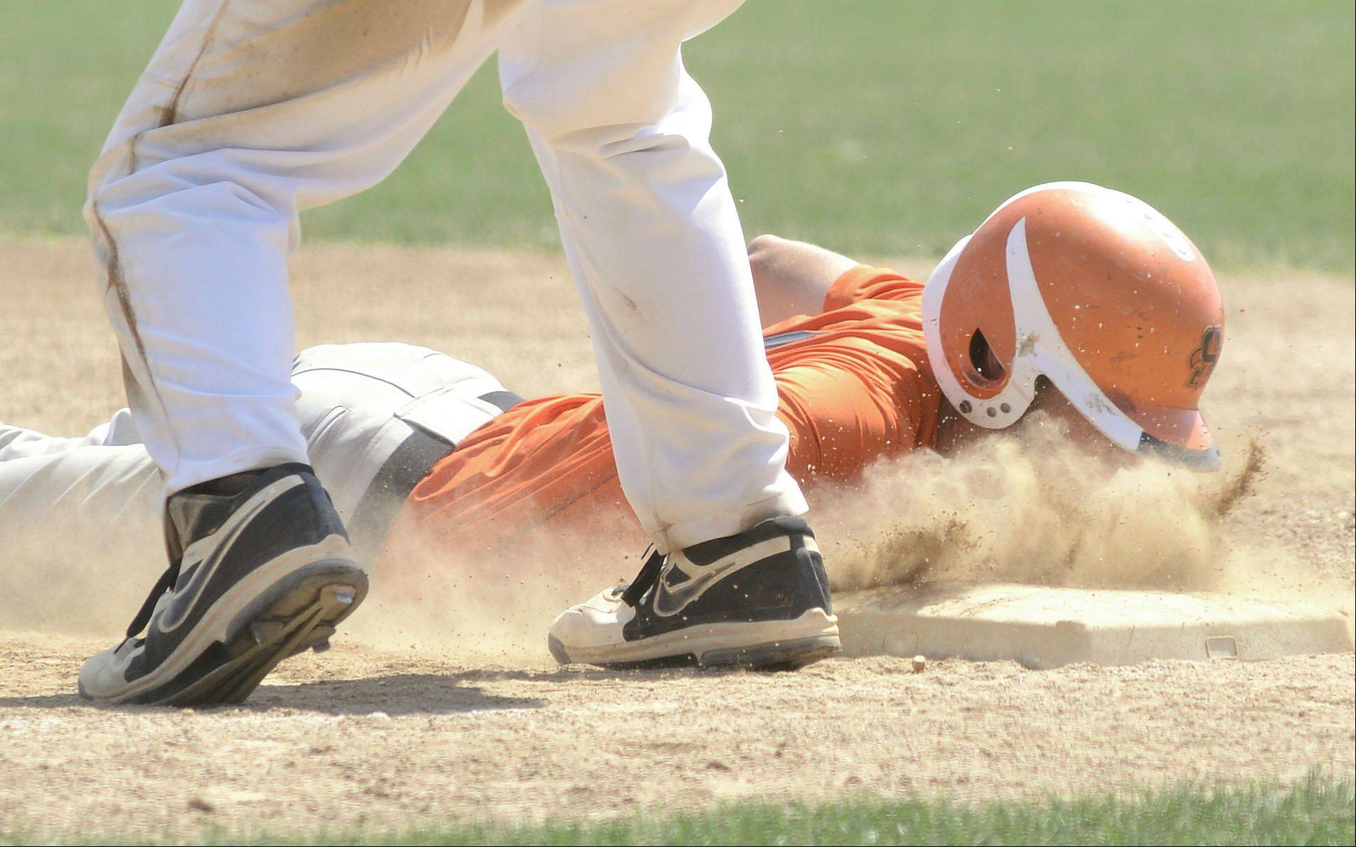 St. Charles East's Alex Abate slides face first back to first base safe from St. Charles North's Joe Kuczek in the third inning of the St. Charles East summer tournament semifinals on Wednesday, July 17.