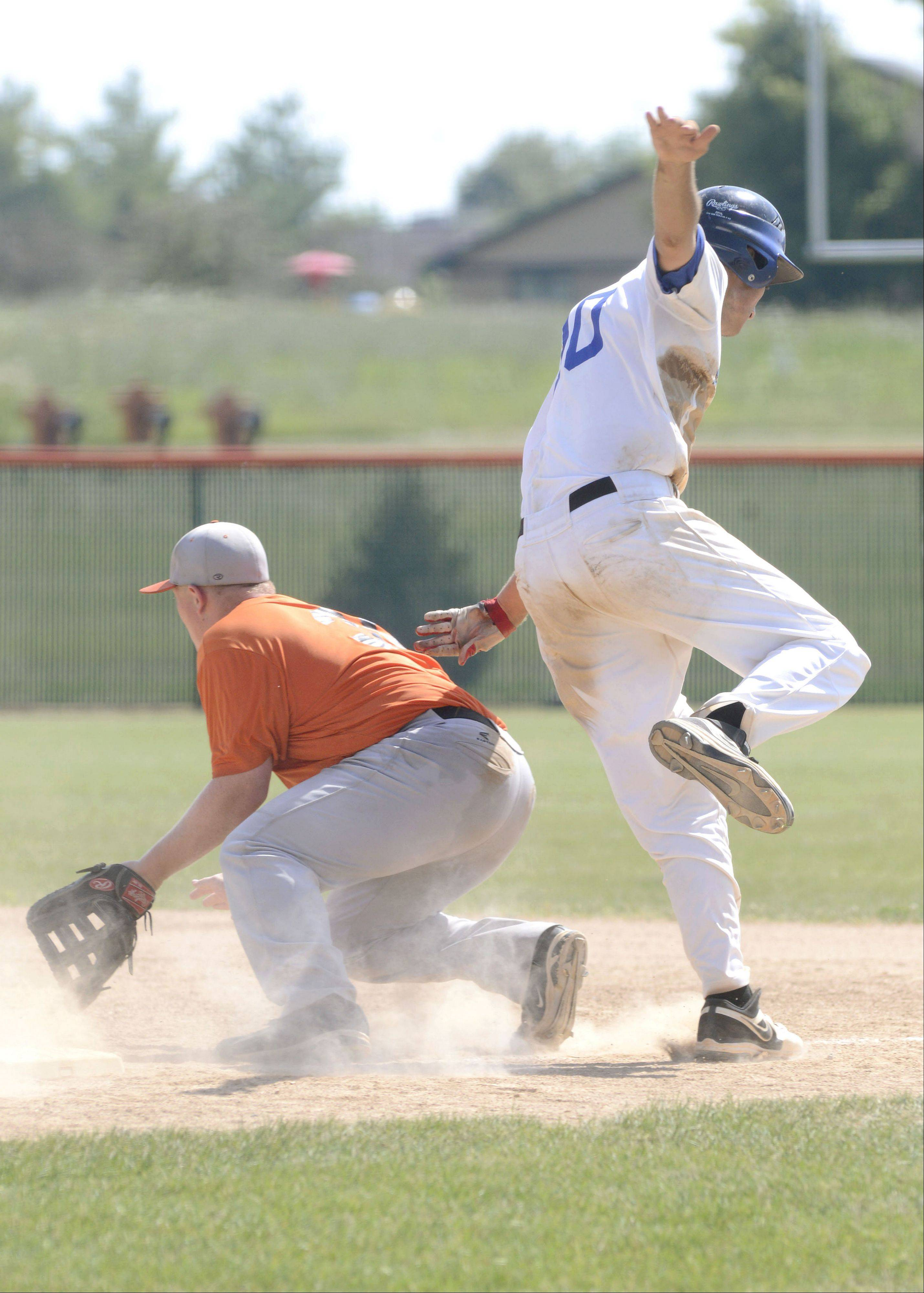 St. Charles North's Joe Kuczek springs off the back of St. Charles East's Ben Smith to avoid a collision while running for first base in the St. Charles East summer tournament semifinals on Wednesday, July 17. Kuczek was safe.
