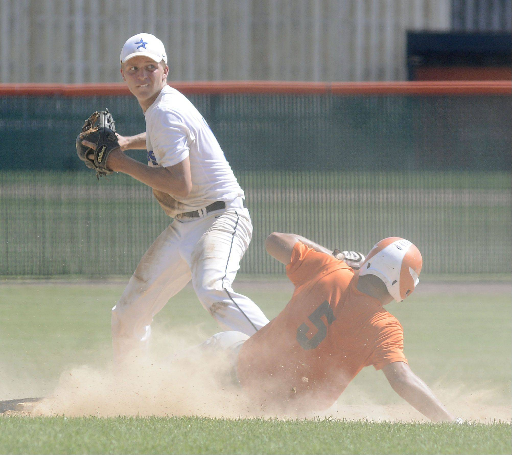 St. Charles East's Erik Anderson is out after an attempt to steal second, and St. Charles North's Luke Johansmeier whips the ball to first base for a double play in the fourth inning of the St. Charles East summer tournament semifinals on Wednesday, July 17.