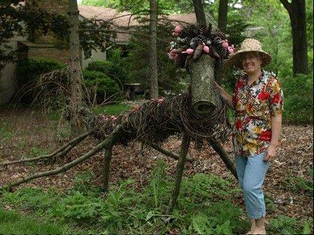 "When Mother Nature blew the top off a large pine tree, artist Kathy Steere created ""Gus, the Guardian of the Storm"" in 2012. After sporting a red and green scarf for the winter, Gus is currently garbed in pink flamingos."