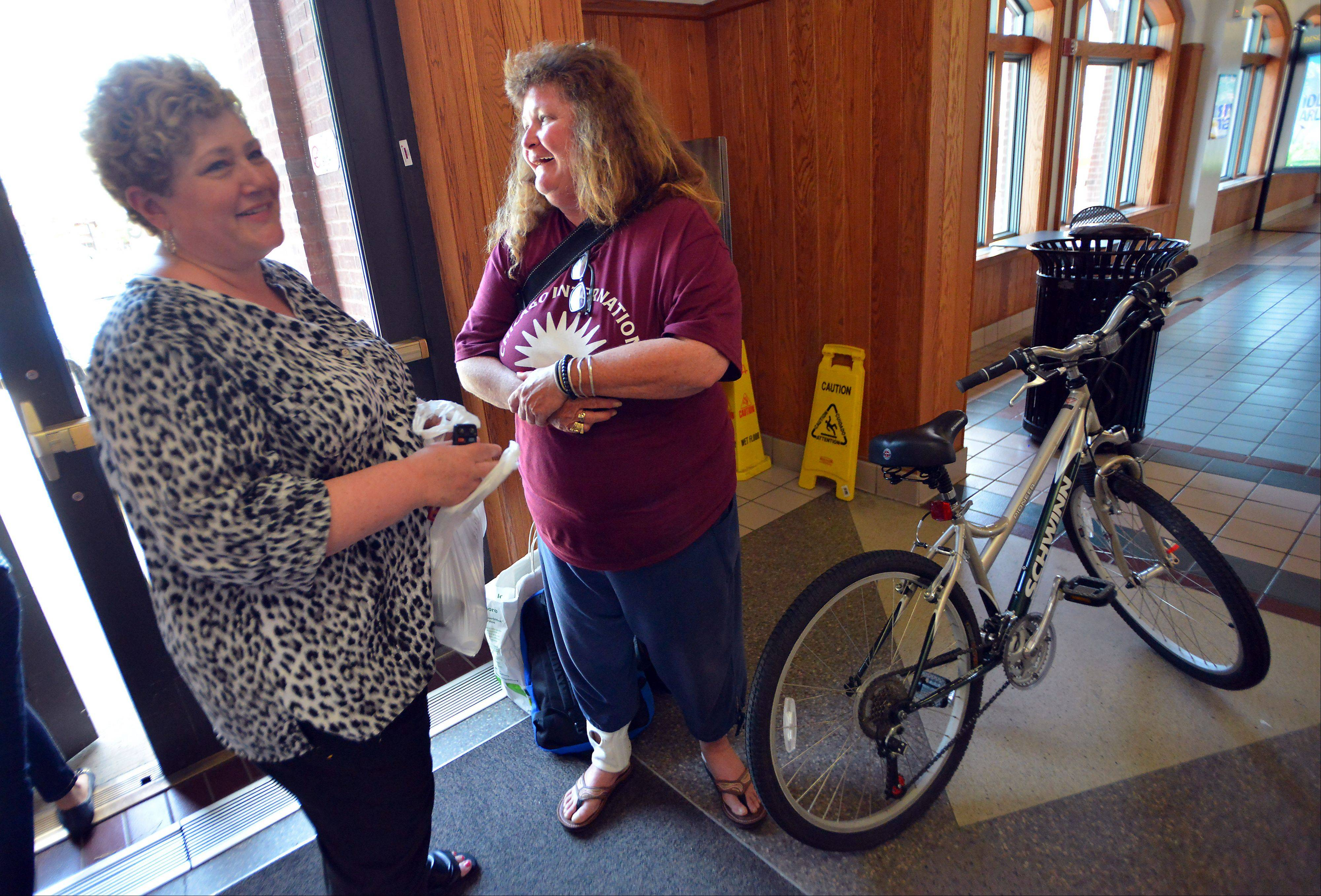 Kathy Kelly of Hoffman Estates, left, gave Rosan Acosta the bike she bought a year ago but barely used. Acosta lost her bike to an arsonist this week.