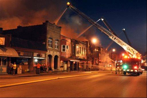Firefighters battle an early morning blaze Monday, July 15, 2013, that destroyed at least five buildings in the small Whiteside County community of Prophetstown. The blaze began in a downtown restaurant around 2 a.m. and spread to at least five nearby buildings.