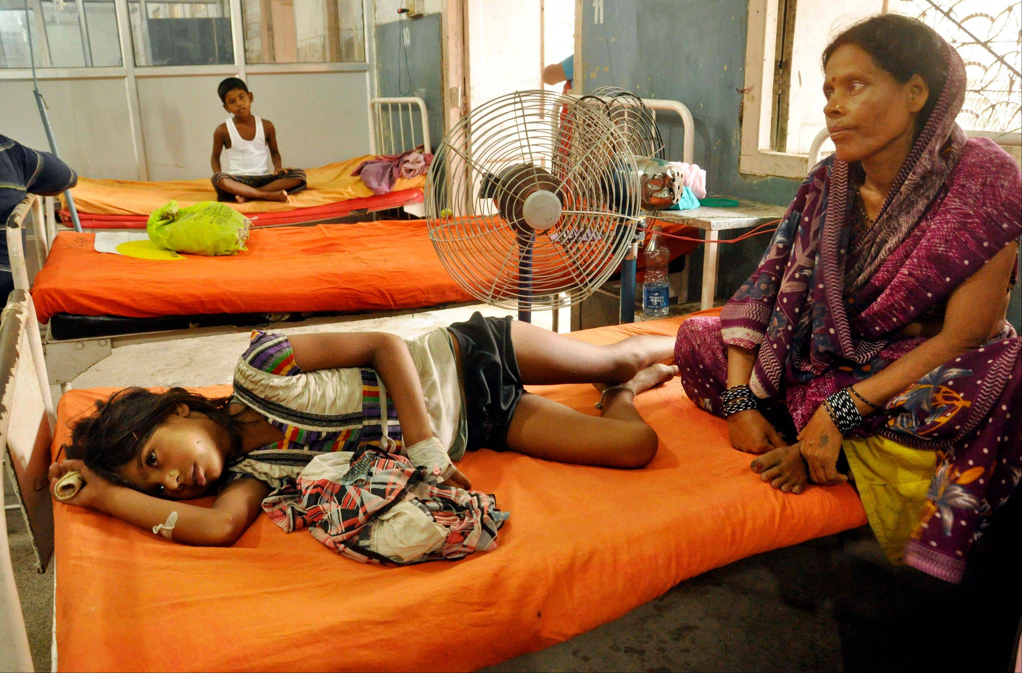 An Indian woman sits beside a child who fell sick after eating a free school lunch, at a hospital in Patna, India, Thursday, July 18, 2013. Indian officials say at least 23 children have died after eating a free school lunch that was tainted with insecticide. India�s midday meal scheme is one of the world�s biggest school nutrition programs, covering some 120 million schoolchildren.