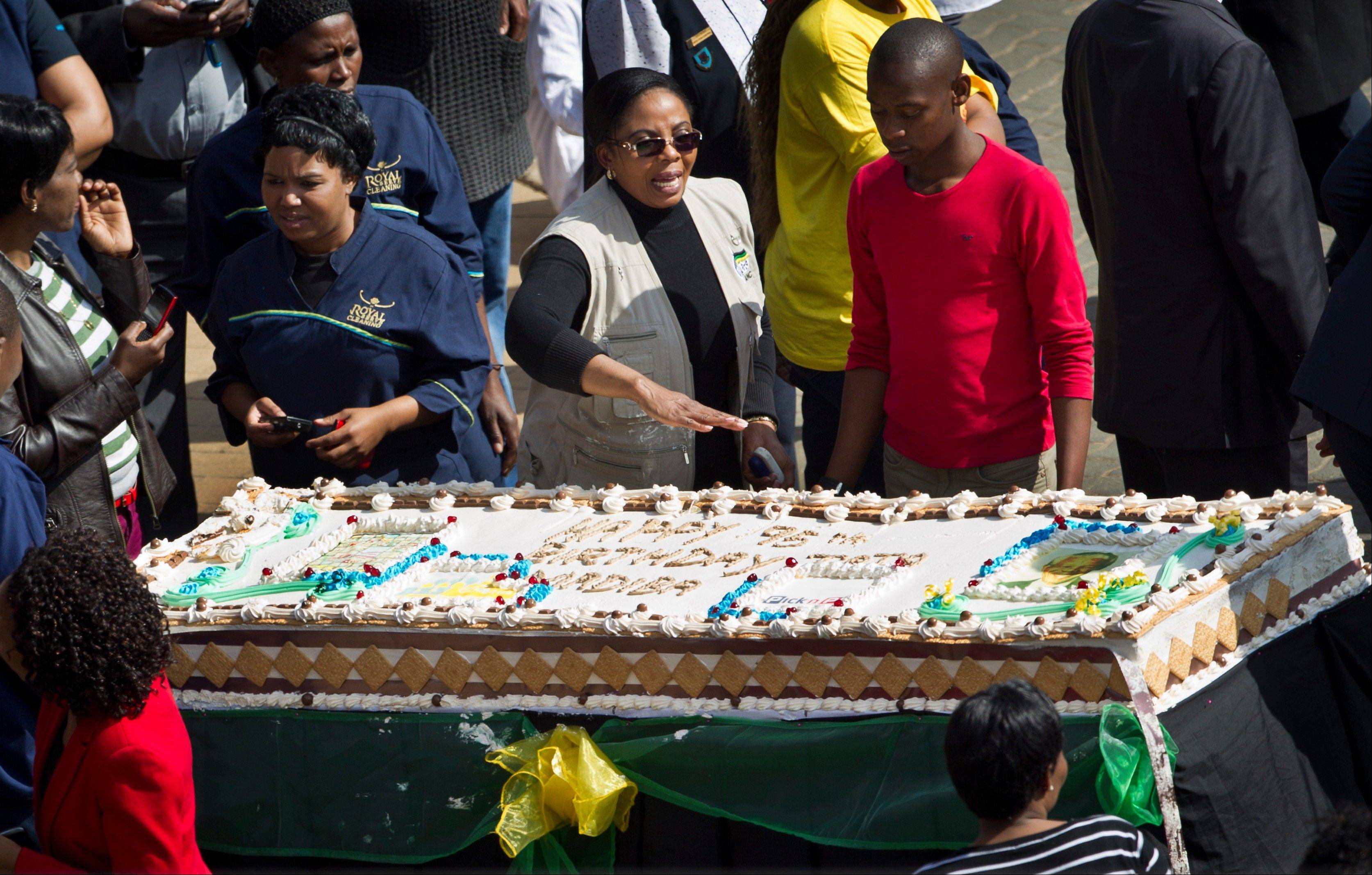 Unidentified guests and hospital workers prepare to cut a large birthday cake for Nelson Mandela inside the gates of the Mediclinic Heart Hospital where former South African President Nelson Mandela is being treated. South Africa celebrated Nelson Mandela�s 95th birthday on Thursday, a milestone capped by news that the former president�s health was improving after fears that he was close to death during ongoing hospital treatment.