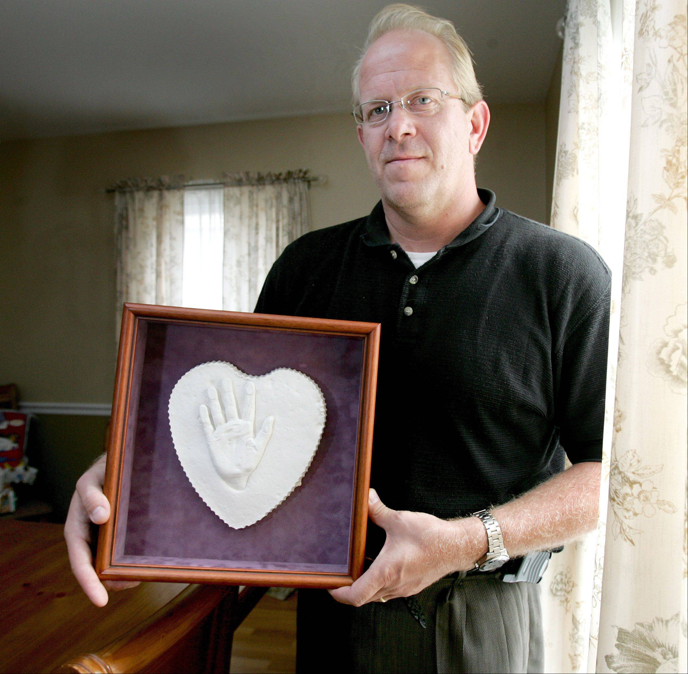Matt Tretter of Glen Ellyn with a plaster mold of his late daughter�s hand, part of a program at Chicago Comer Children�s Hospital. This will be the final year Tretter will hold his Caitlin�s Cause fundraising event.