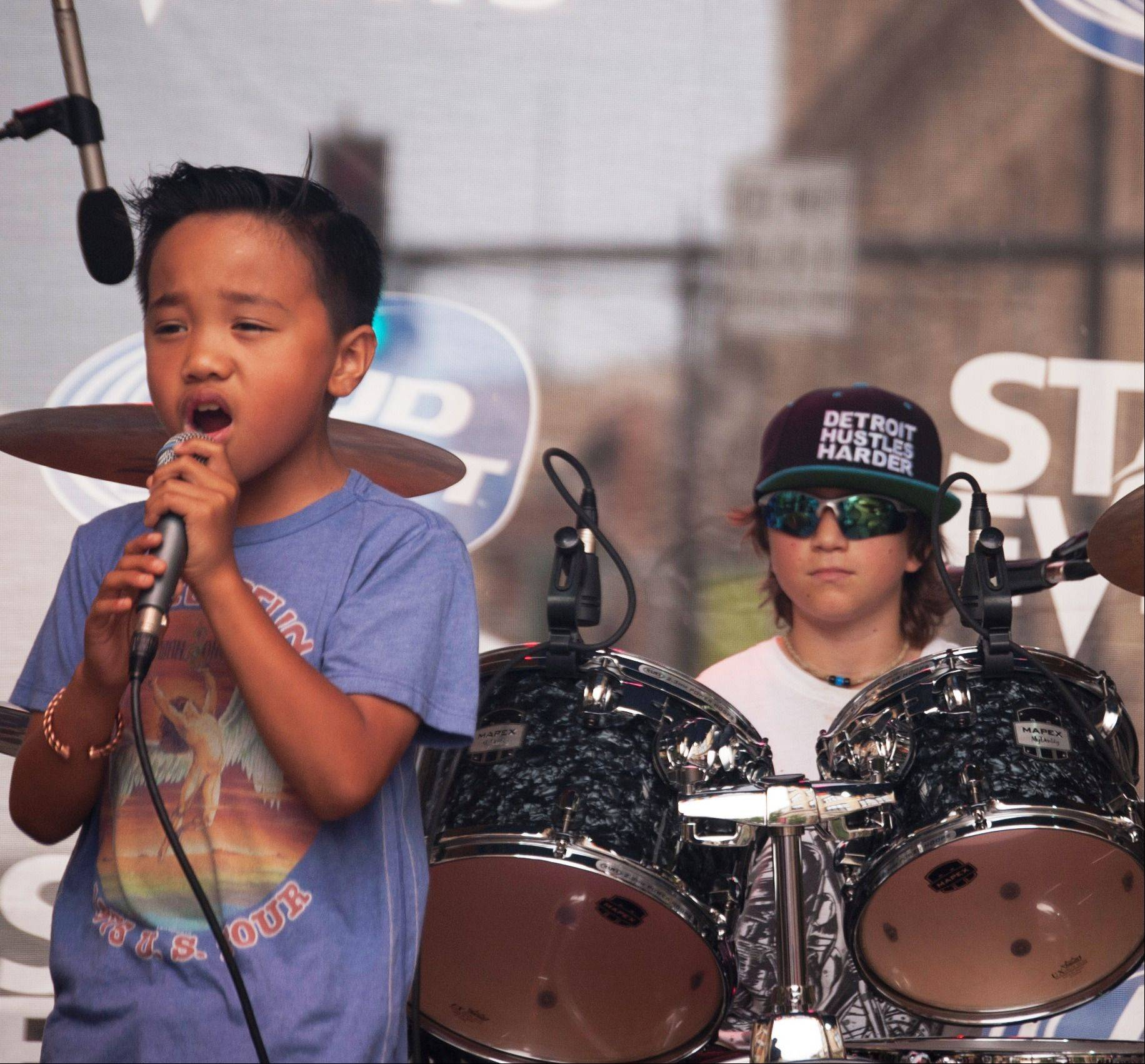 Lead vocalist Nikko Viejon, 8, of North Aurora, with drummer Cohen Bessler, 10, of St. Charles, in the background, during LiveWire's performance July 6 at Taste of Lakeview in Chicago.