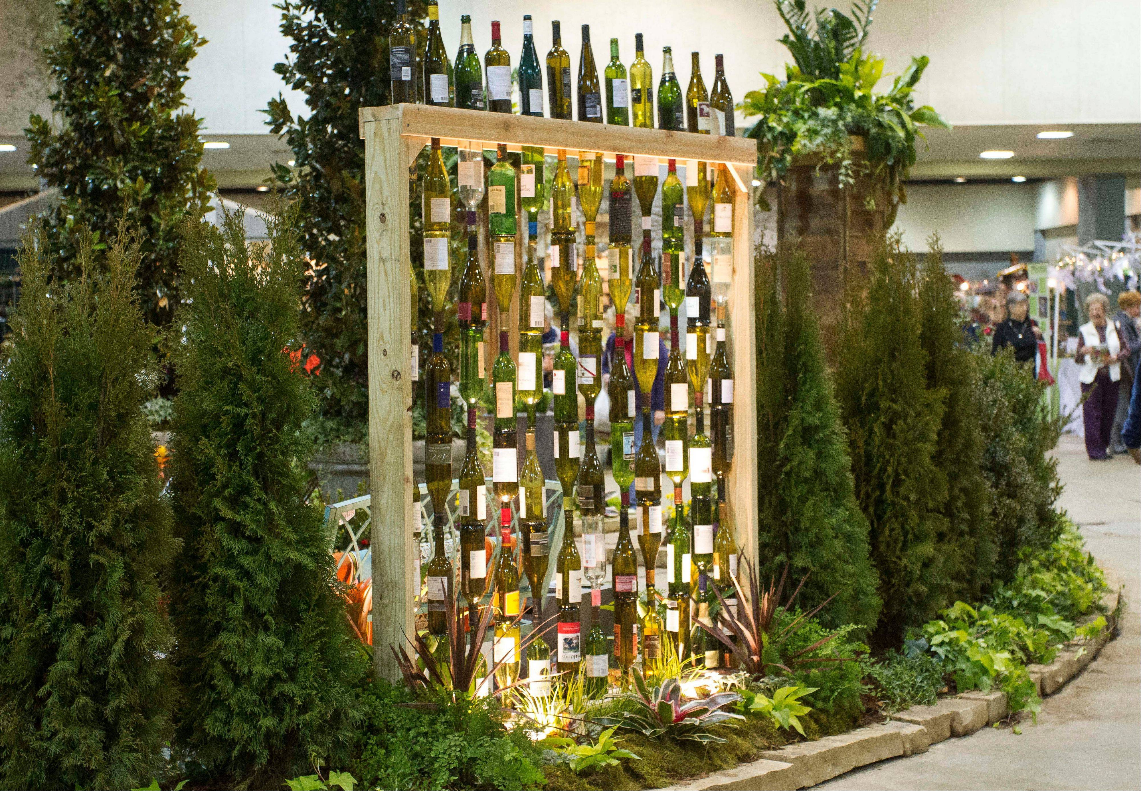 "In this publicity photo provided by Chris H. Olsen, the Landscape Designer, Olsen, of Little Rock, Ark., created a decorative wall out of empty wine bottles by threading them onto metal poles inserted into a wooden frame. Olsen shares outdoor decorating ideas in his book ""Chris H. Olsen's Five Seasons"" (Leisure Arts, 2011)."