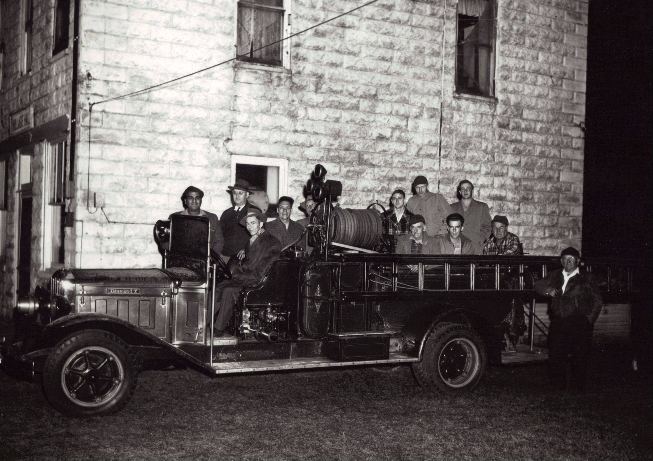 "Bernard ""Barney"" Medina, far left, is pictured here with the first fire truck of the Pingree Grove & Countryside Fire Protection District, which he helped found as an all-volunteer operation with his brother-in-law John J. Schmitz in 1947."