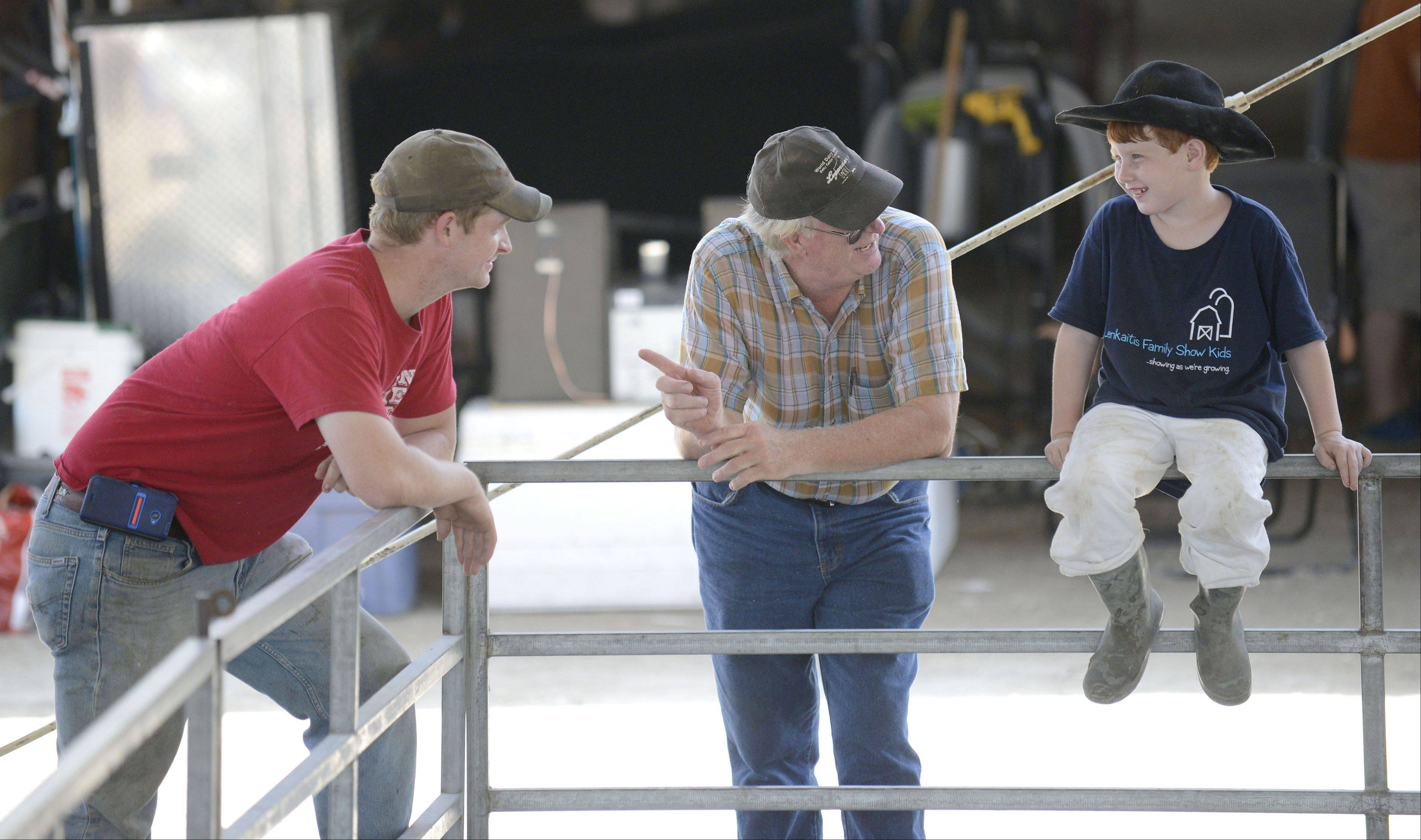 Philip Shanks, left, of Garden Prairie, Ill., listens to his father, David, tell Caden Lenkaitis, 7, of Campton Hills about how Philip started showing at fairs, including the Kane County Fair, when he was about 4 years old. The families are longtime friends.
