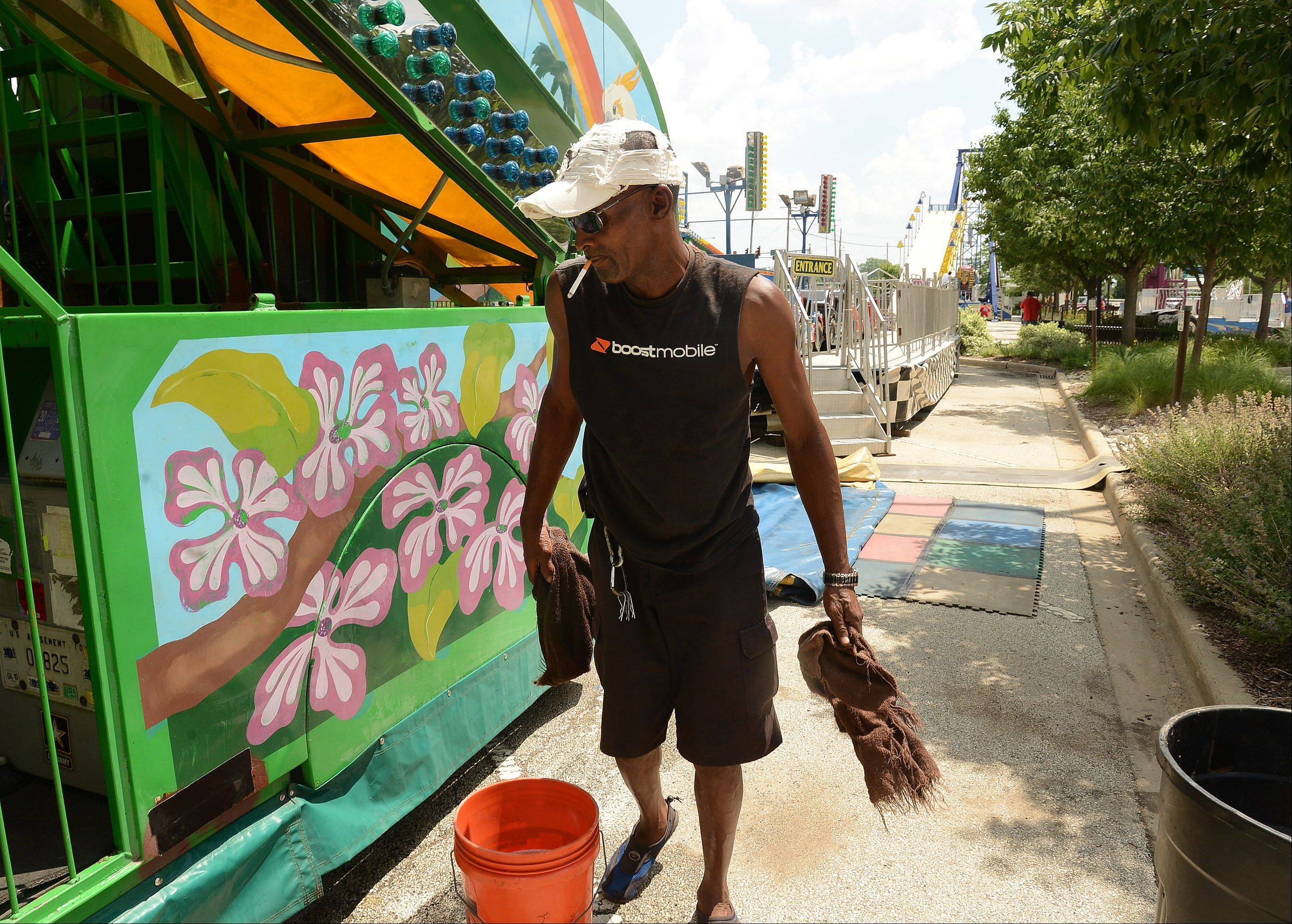 Eddie Wellington of D&J Amusements washes down the Rainbow Rock ride Thursday in preparation for Des Plaines Summer Fling in downtown Des Plaines. The three-day festival highlighted by live music, food, games and carnival rides kicks off Friday.