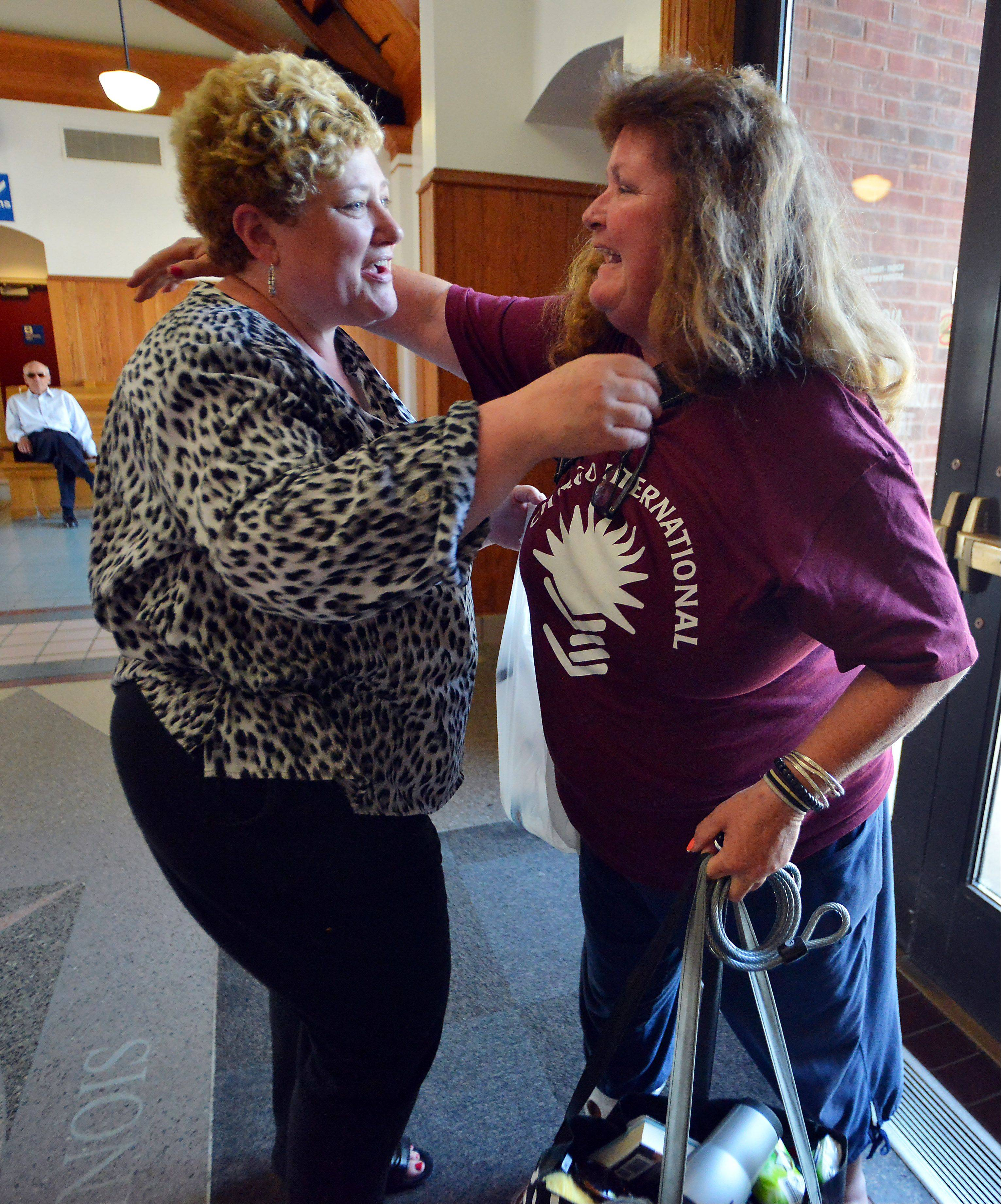 Kathy Kelly of Hoffman Estates, left, gets a hug from Rosan Acosta.