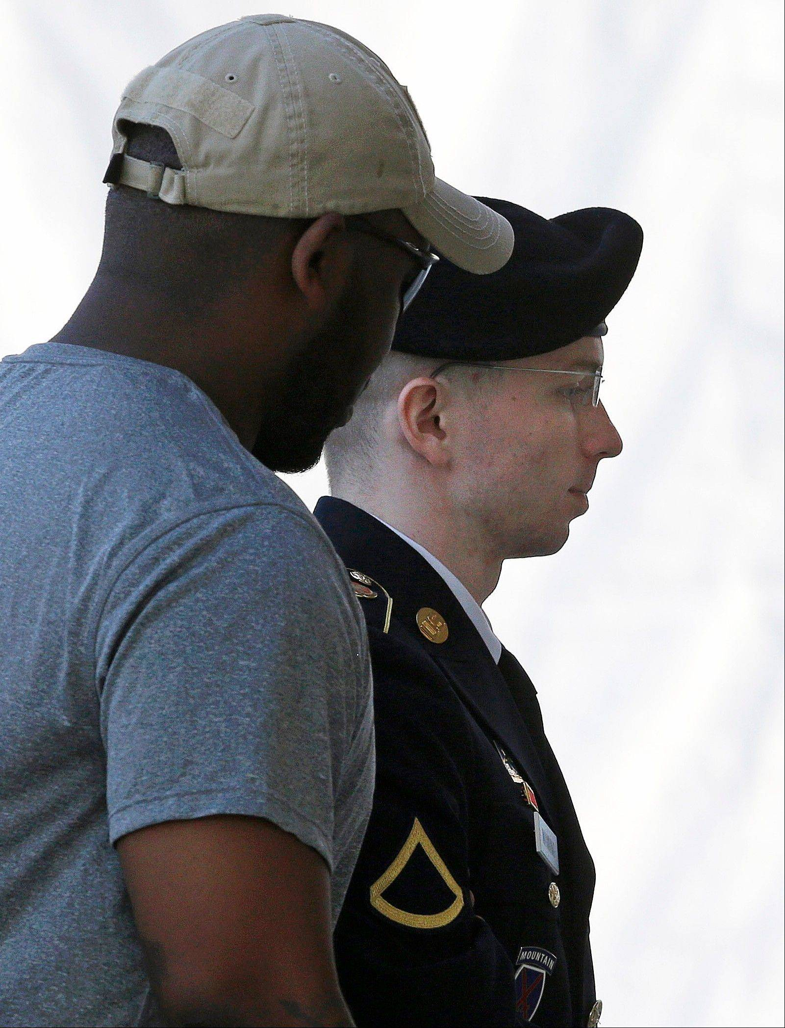 Army Pfc. Bradley Manning, right, is escorted into a courthouse at Fort Meade, Md., Thursday, July 18, 2013, before a court martial hearing. A military judge refused Thursday to dismiss the most serious charge against Manning, the Army private who gave reams of classified information to the anti-secrecy website WikiLeaks.