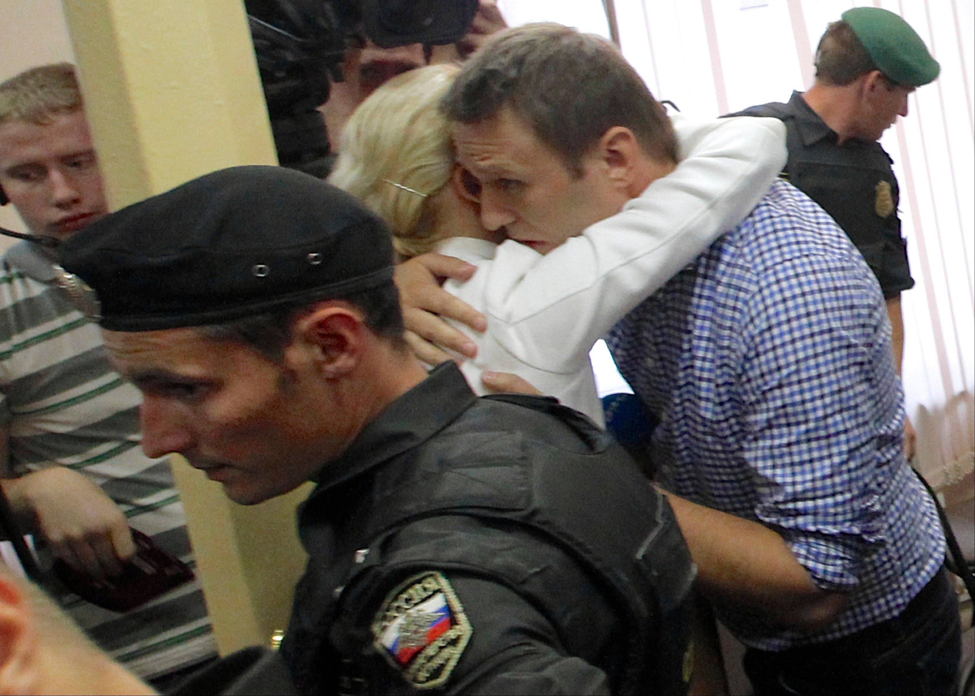 Russian opposition leader Alexei Navalny, embraces his wife Yulia at a court in Kirov, Russia Thursday, July 18, 2013. Alexei Navalny, one of the Russian opposition's leading figures, was convicted of embezzlement Thursday and sentenced to five years in prison.