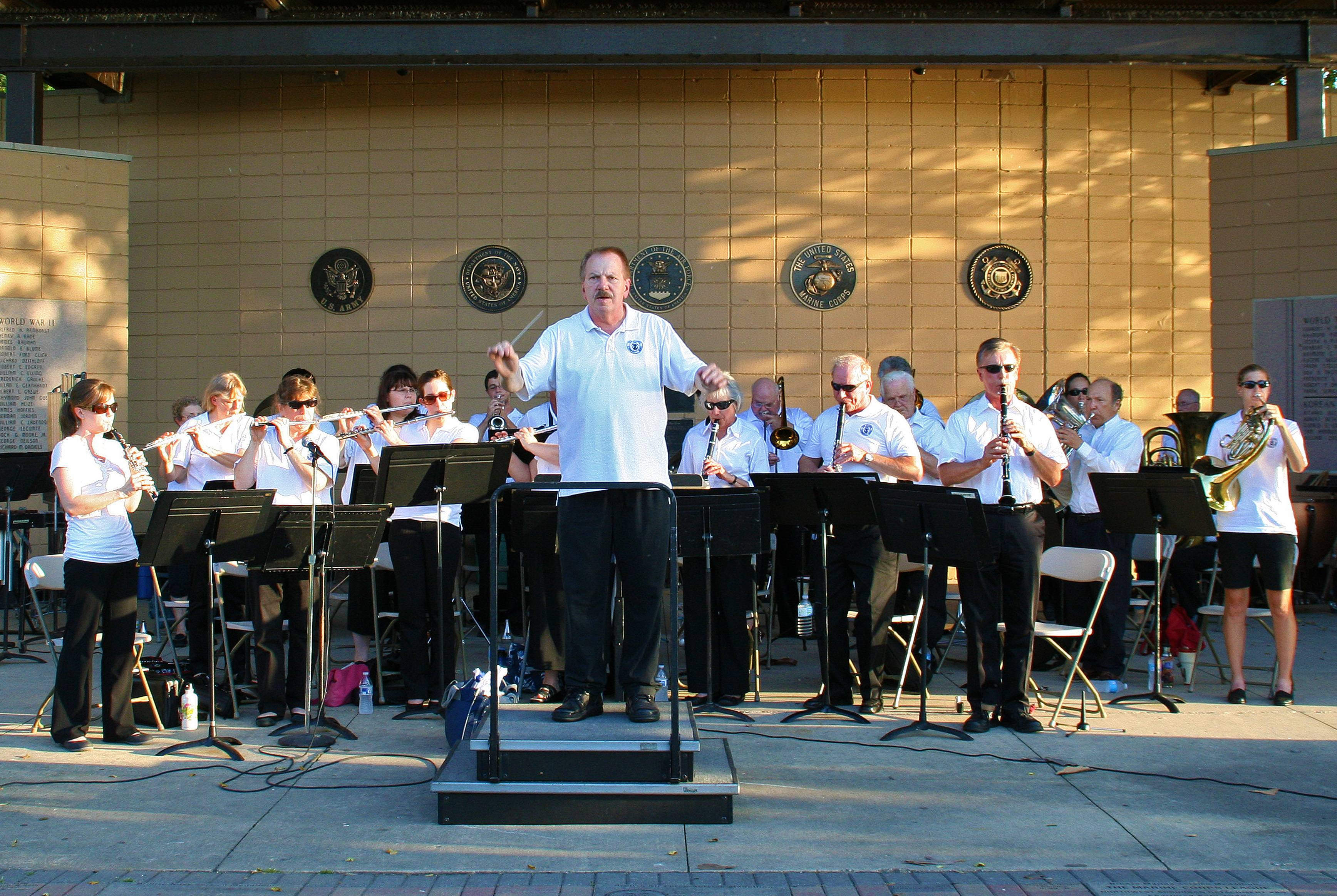 The Des Plaines Community Concert Band, under the direction of Larry J. Carle, performs The Star Spangled Banner, at the Lake Park Memorial Pavilion on July 18.